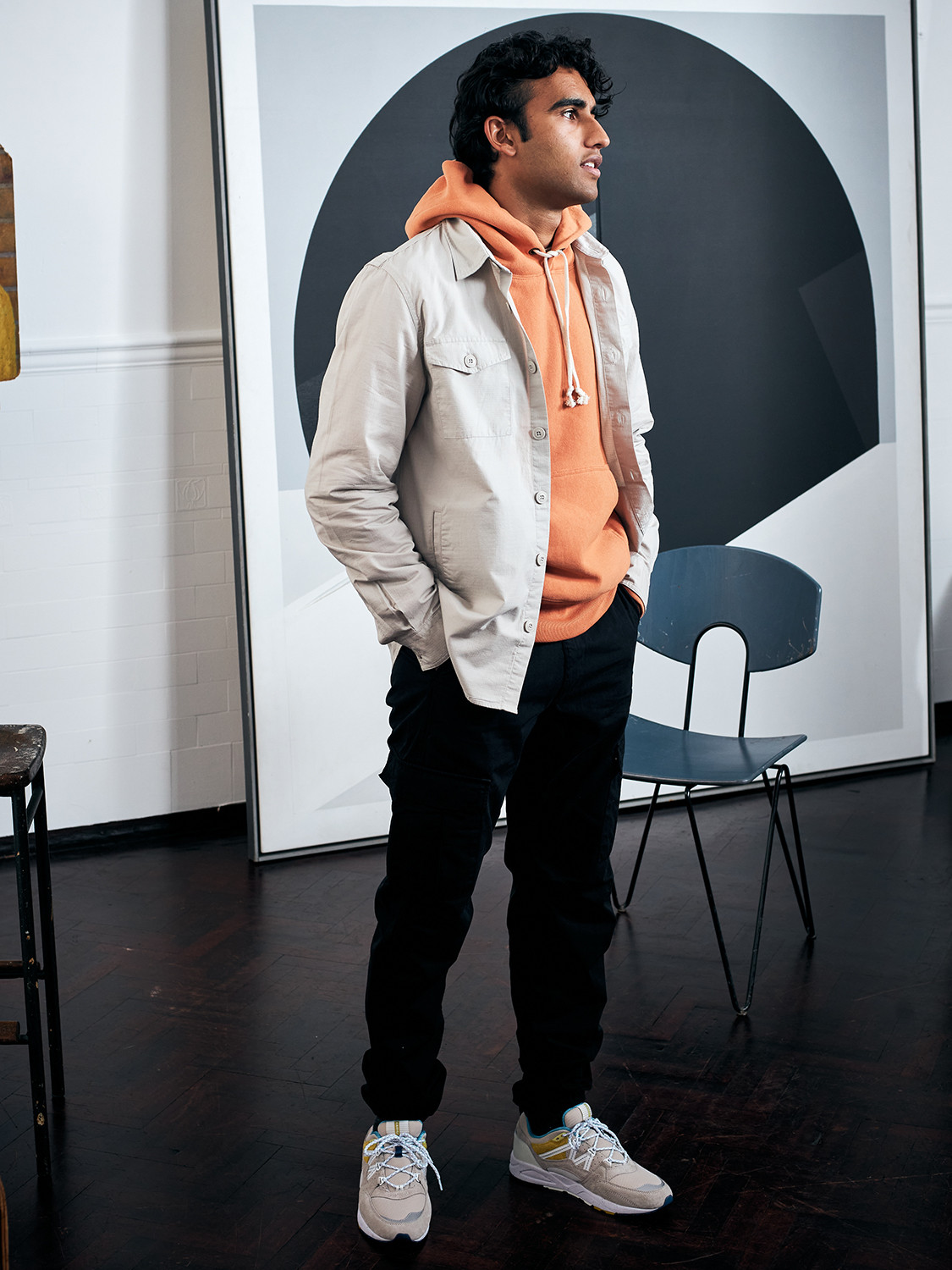 Men's outfit idea for 2021 with neutral overshirt, orange plain hoodie, black chinos, neutral sneakers. Suitable for spring, fall and winter.