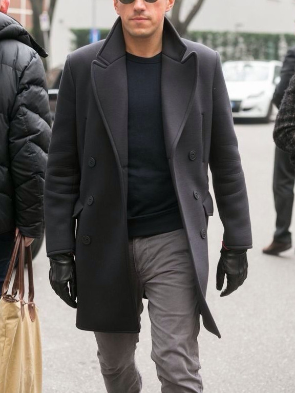 Men's outfit idea for 2021 with grey single-breasted overcoat, black crew neck knitted sweater, grey jeans, leather gloves, black chelsea boots. Suitable for fall and winter.