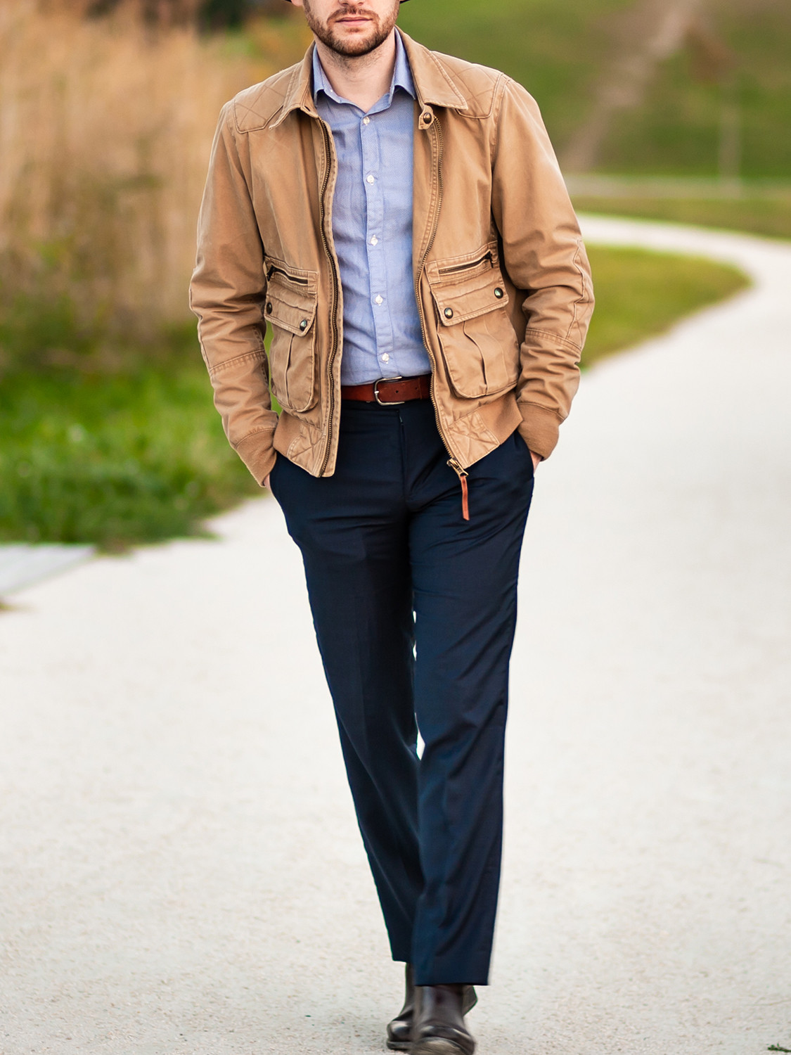 Men's outfit idea for 2021 with neutral field jacket, blue casual shirt, navy dress pants, oxford / derby shoes. Suitable for spring and fall.