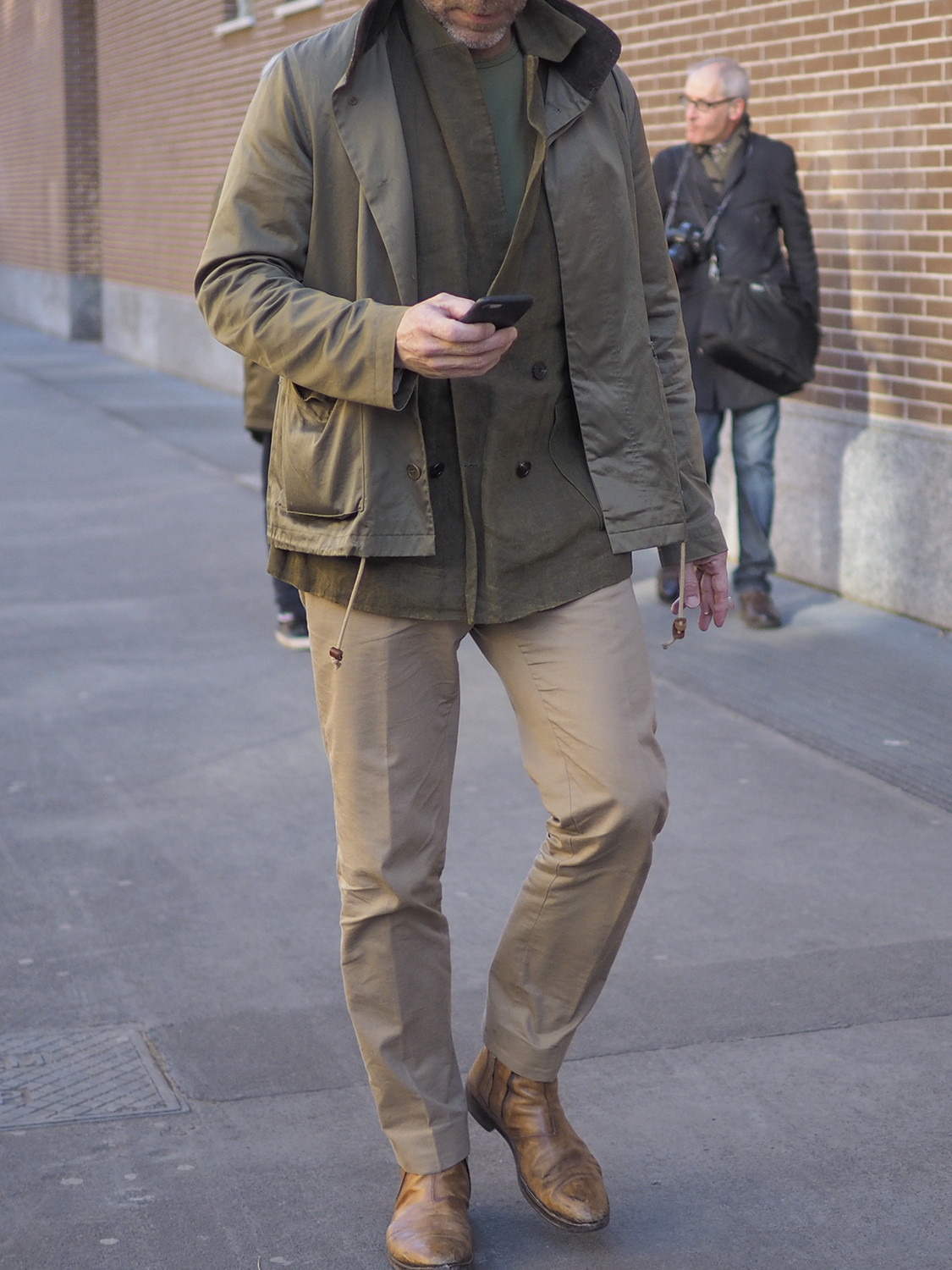 Men's outfit idea for 2021 with green utility jacket, green plain crew neck t-shirt, stone chinos, brown chelsea boots. Suitable for spring and autumn.