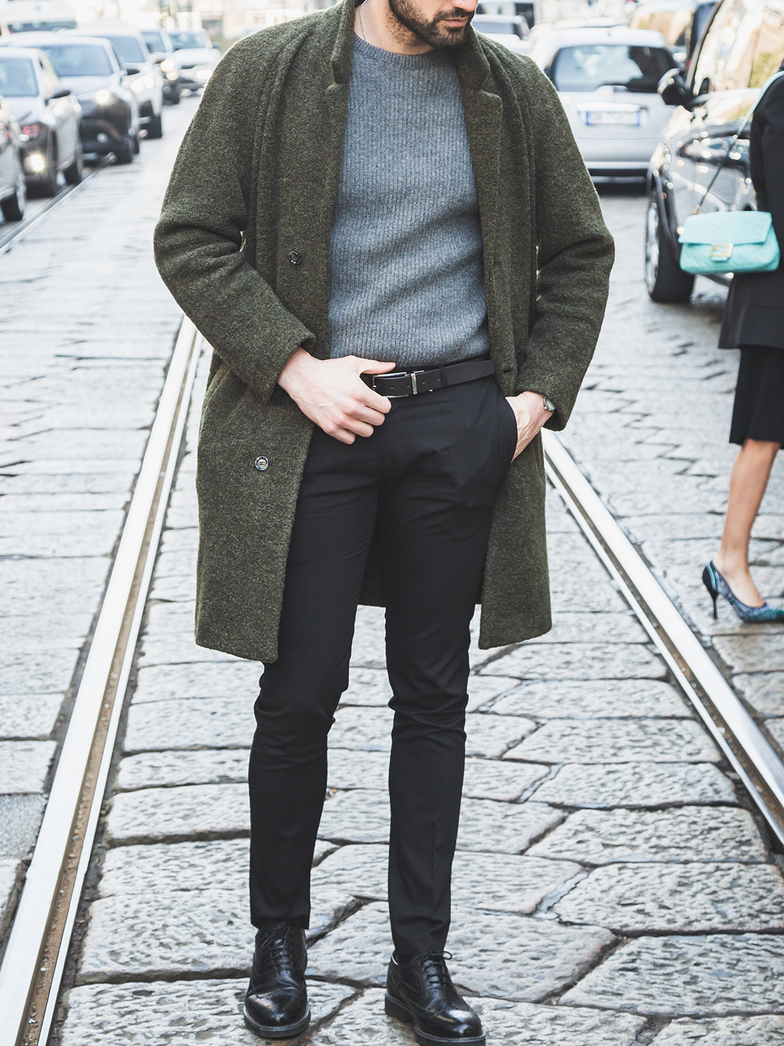 Men's outfit idea for 2021 with green single-breasted overcoat, grey plain crew neck knitted jumper, black formal trousers, black brogues. Suitable for autumn and winter.