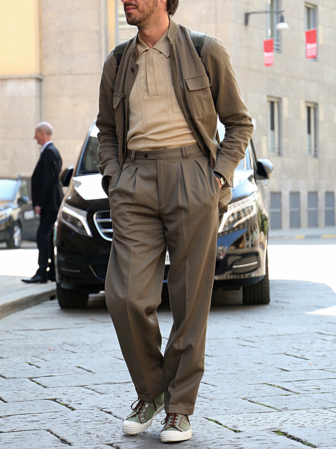 Men's outfit idea for 2021 with neutral harrington jacket, neutral plain short-sleeved polo, neutral chinos, green rucksack, neutral trainers. Suitable for spring, summer and autumn.