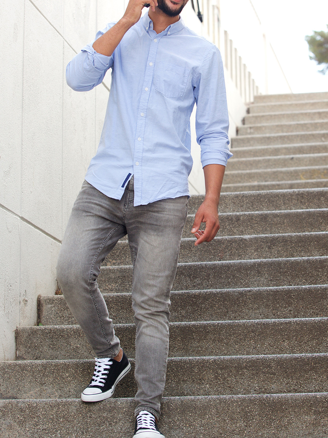 Men's outfit idea for 2021 with blue casual shirt, gray jeans, brown casual belt, black sneakers. Suitable for spring and fall.