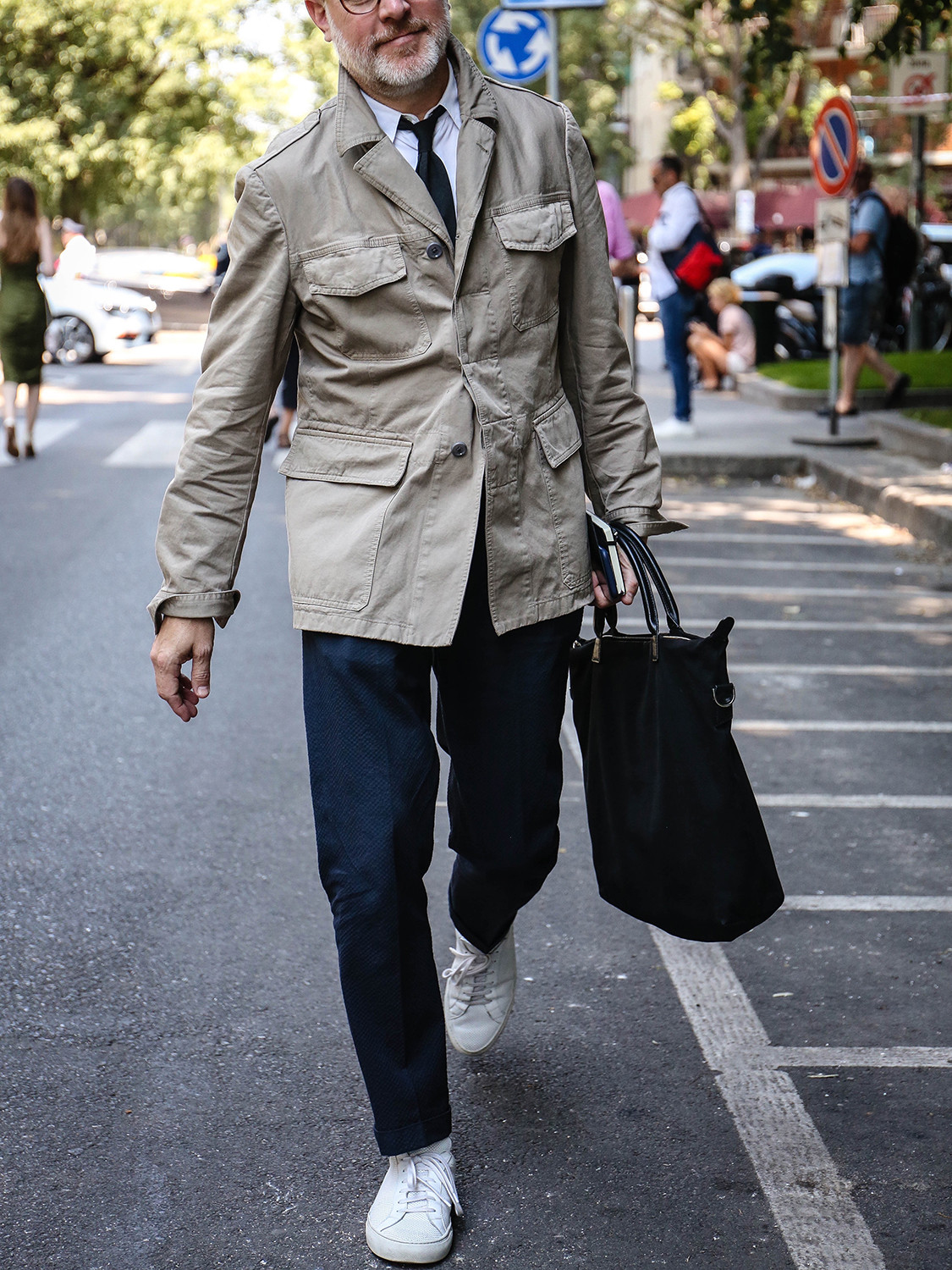 Men's outfit idea for 2021 with neutral utility jacket, white formal shirt, navy formal trousers, white trainers. Suitable for spring, summer and autumn.