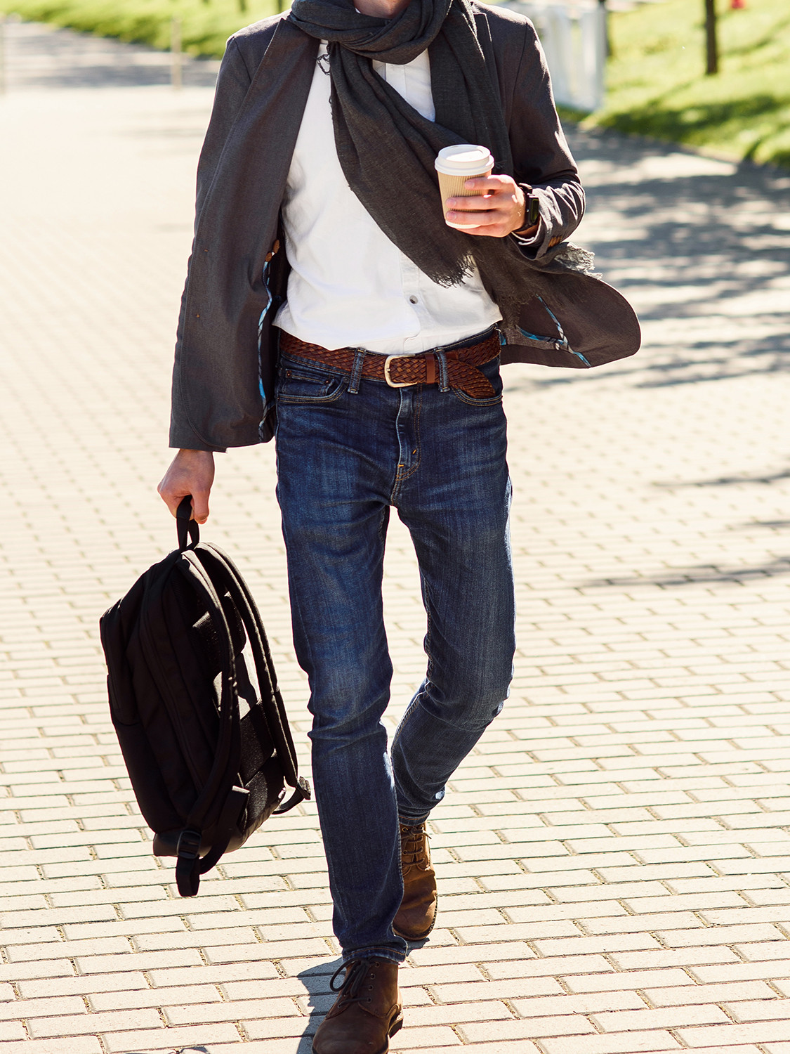 Men's outfit idea for 2021 with gray blazer, white casual shirt, mid blue jeans, black backpack, brown chukka boots. Suitable for spring and fall.