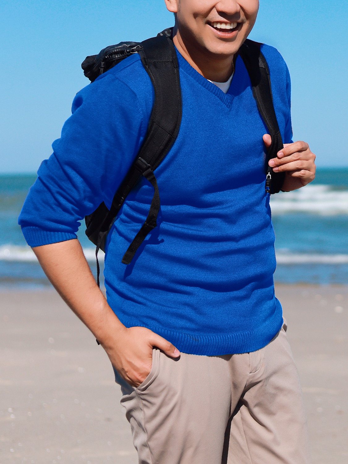 Men's outfit idea for 2021 with blue plain v-neck knitted sweater, white crew neck t-shirt, black backpack. Suitable for spring and fall.