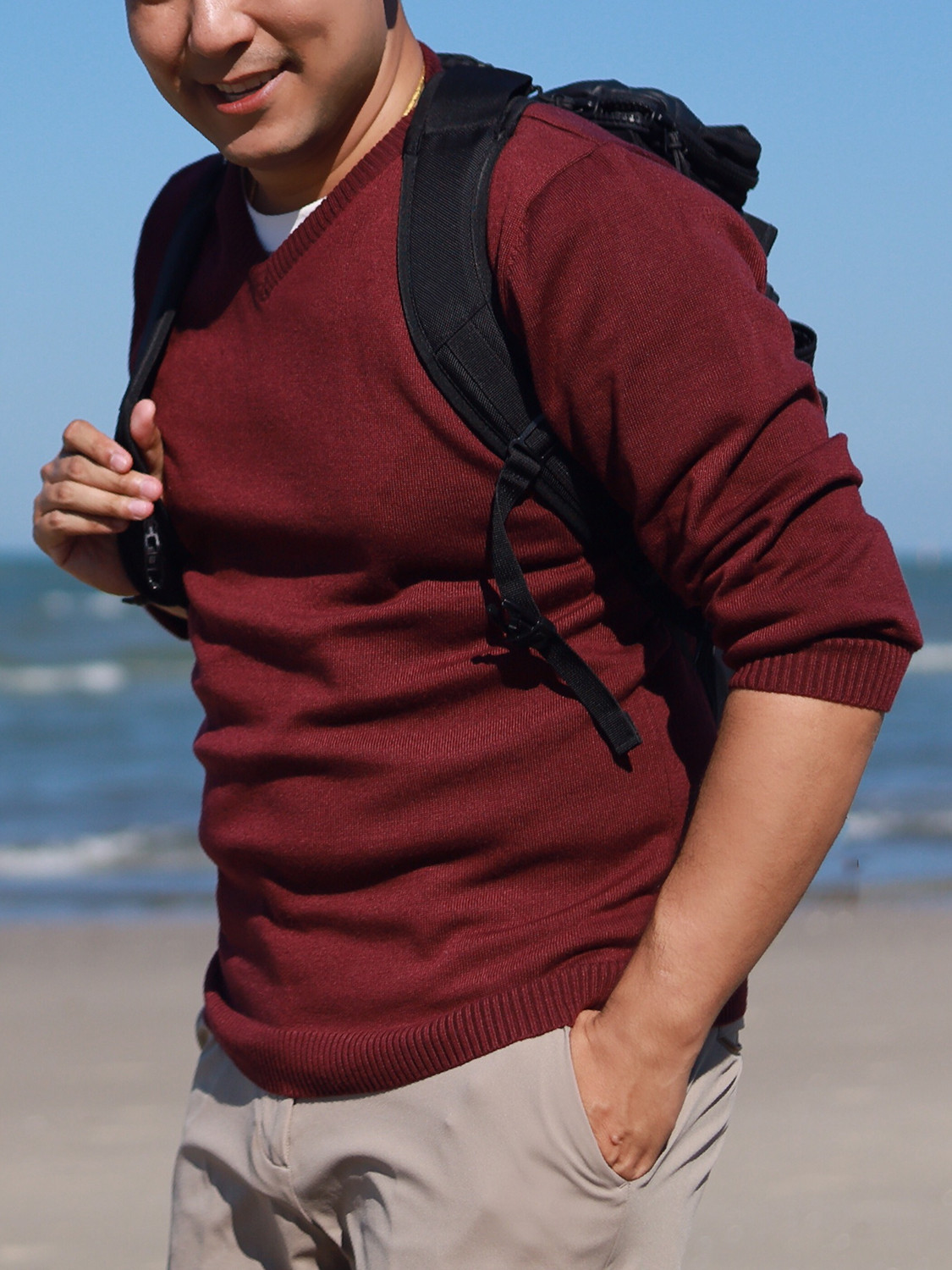 Men's outfit idea for 2021 with red plain crew neck knitted sweater, white crew neck t-shirt, stone chinos, black backpack, white sneakers. Suitable for spring and fall.