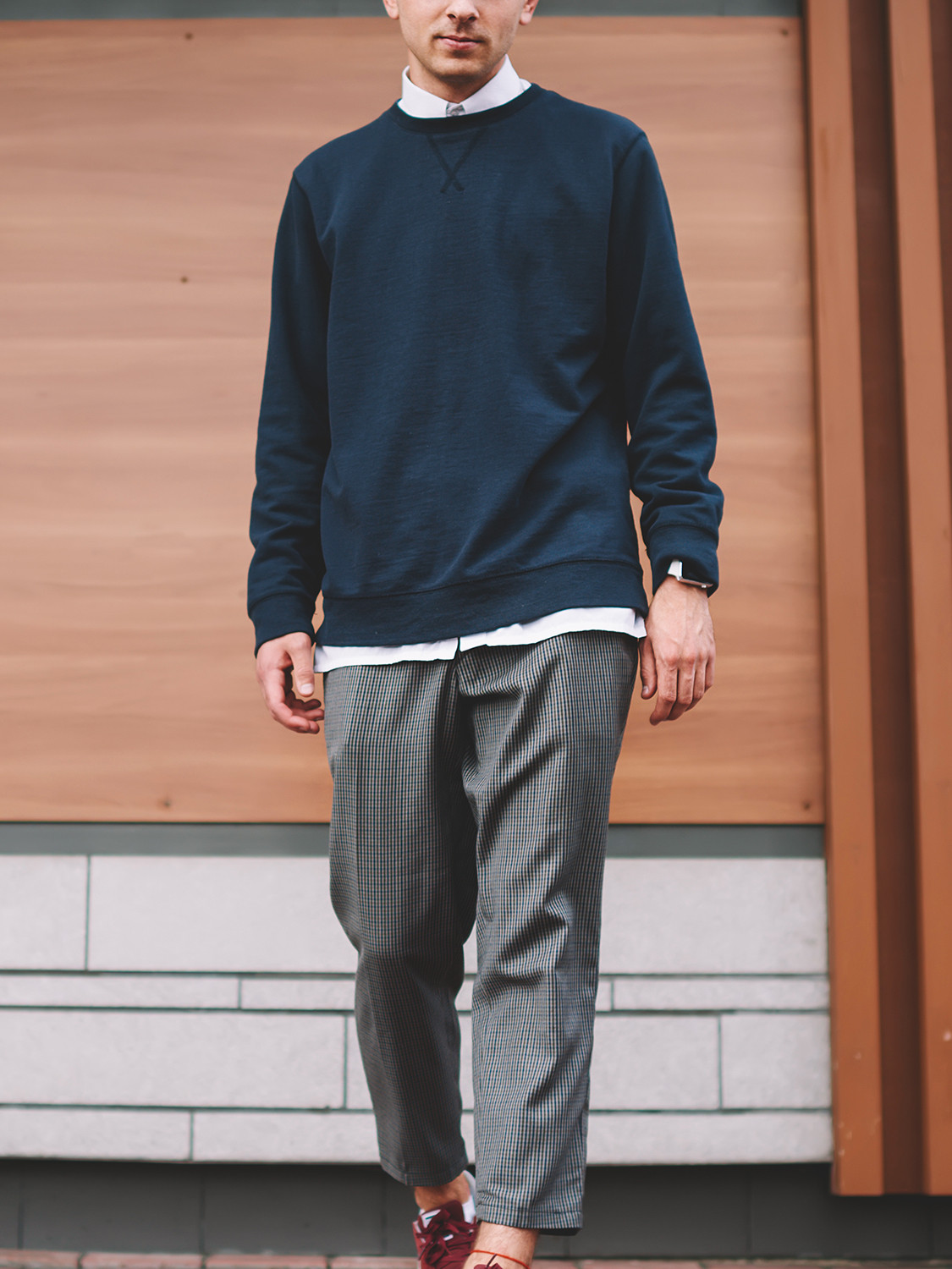 Men's outfit idea for 2021 with navy plain sweatshirt, white casual shirt, grey formal trousers, red everyday trainers. Suitable for spring, autumn and winter.