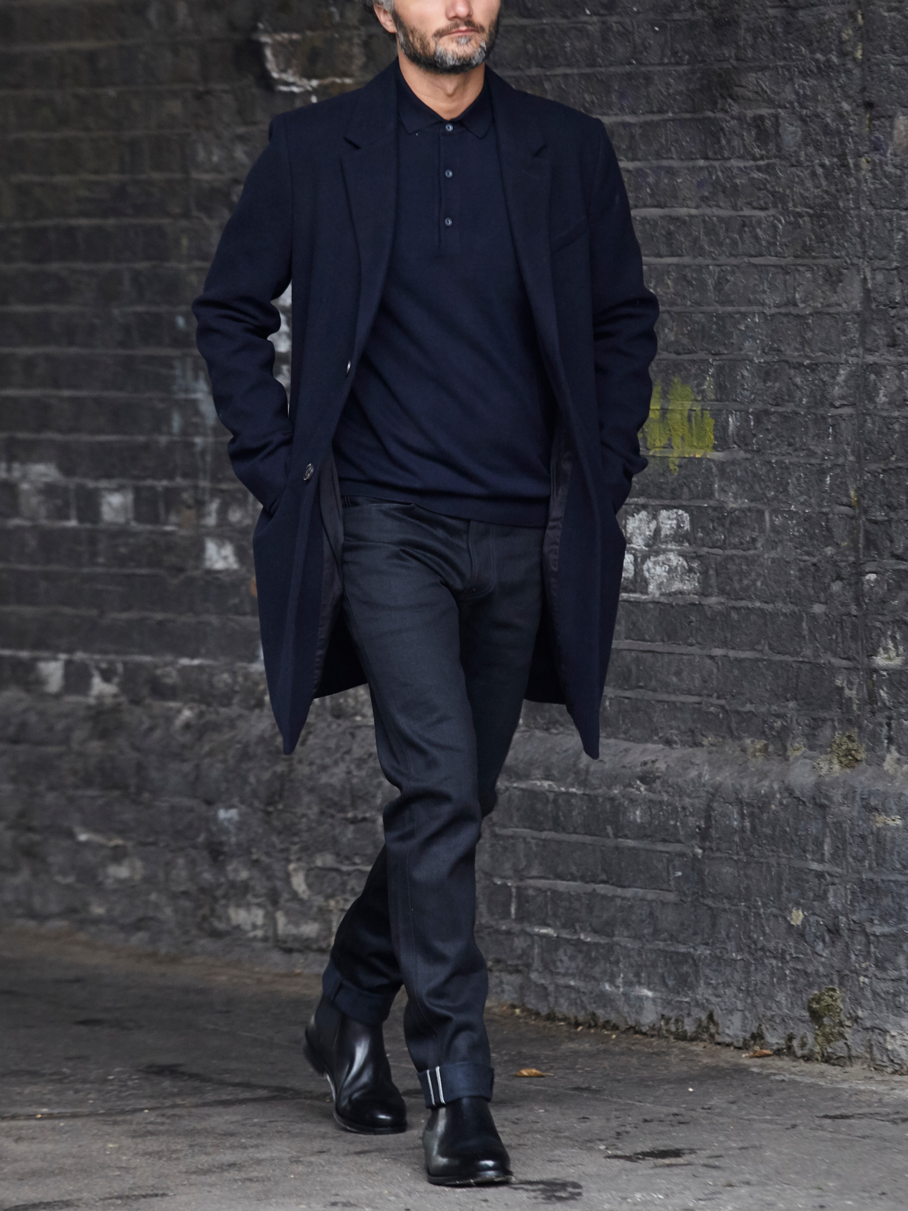 Men's outfit idea for 2021 with single-breasted overcoat, navy long-sleeved polo, black chinos, black chelsea boots. Suitable for fall and winter.