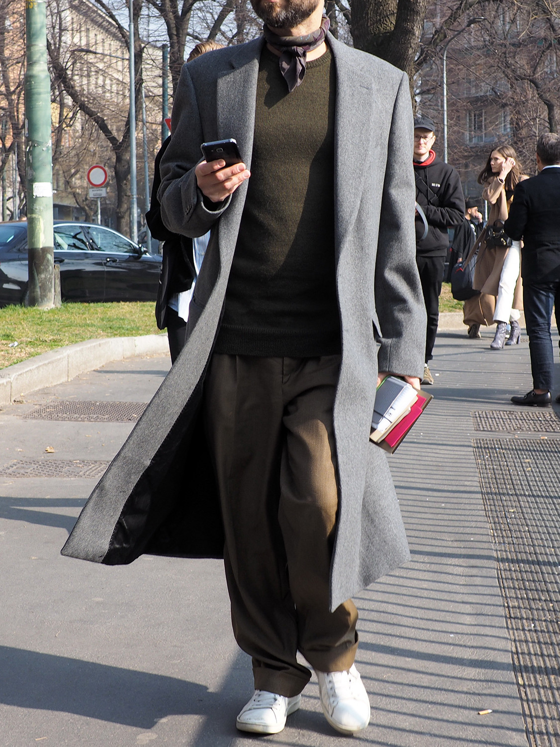 Men's outfit idea for 2021 with grey single-breasted overcoat, green plain crew neck knitted jumper, brown chinos, white trainers. Suitable for autumn and winter.