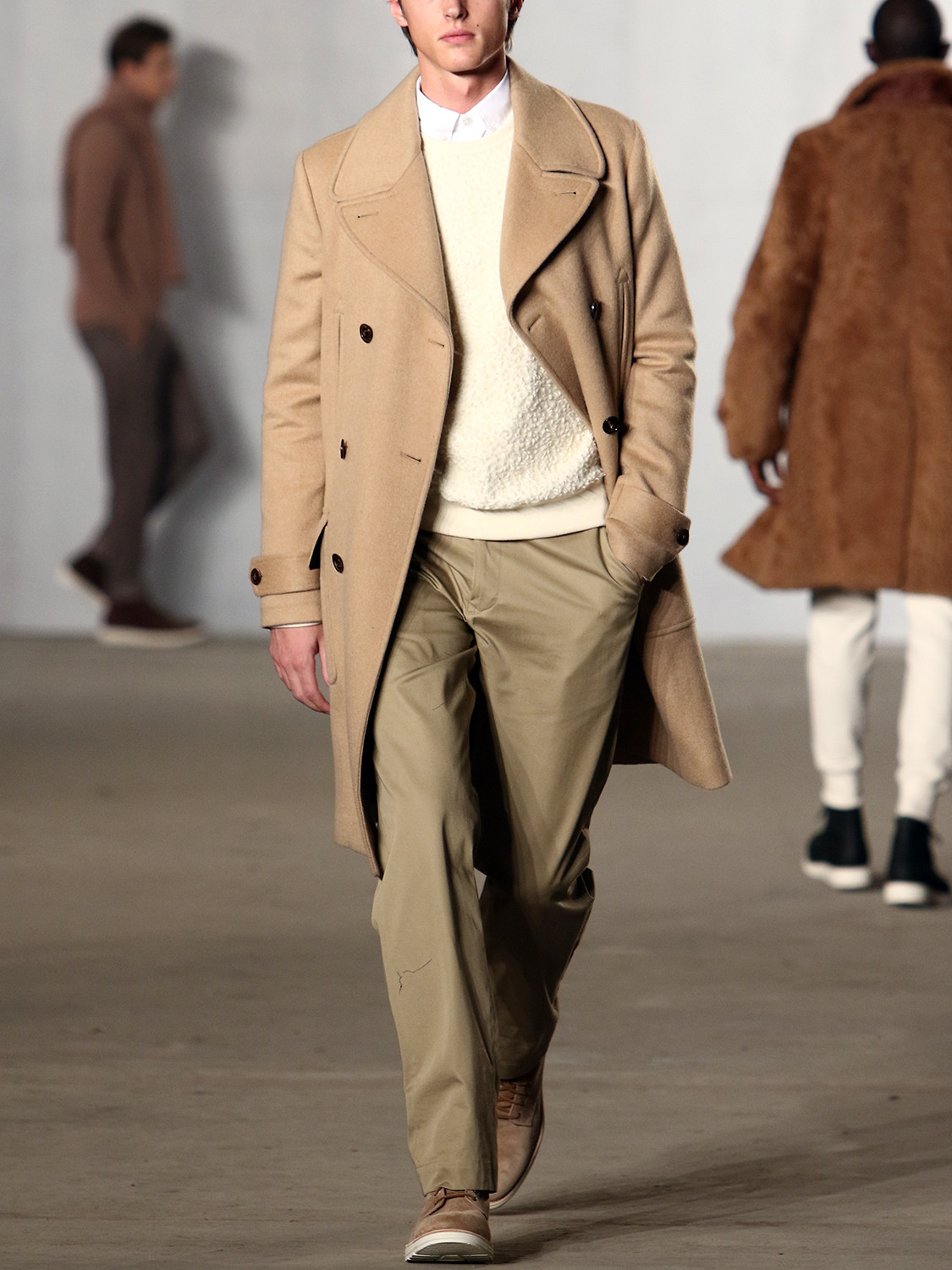 Men's outfit idea for 2021 with camel coat, neutral plain sweatshirt, white casual shirt, neutral chinos, neutral desert boots. Suitable for autumn.