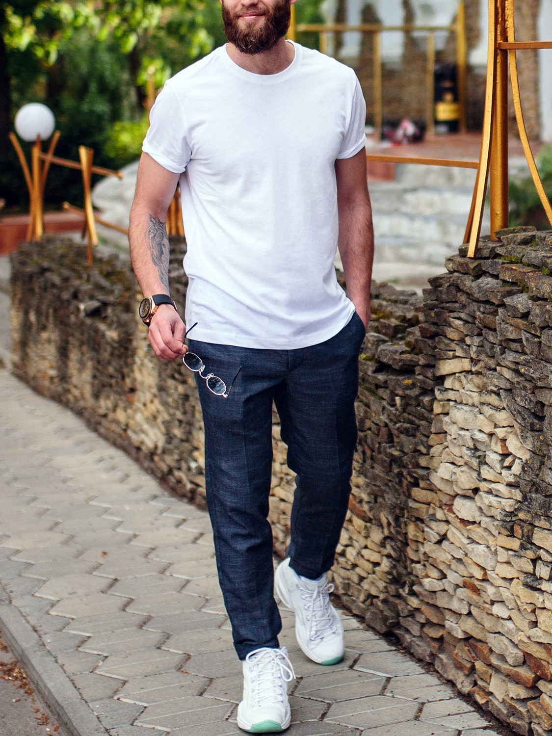 Men's outfit idea for 2021 with white crew neck t-shirt, navy plain dress pants, white everyday sneakers. Suitable for spring and fall.