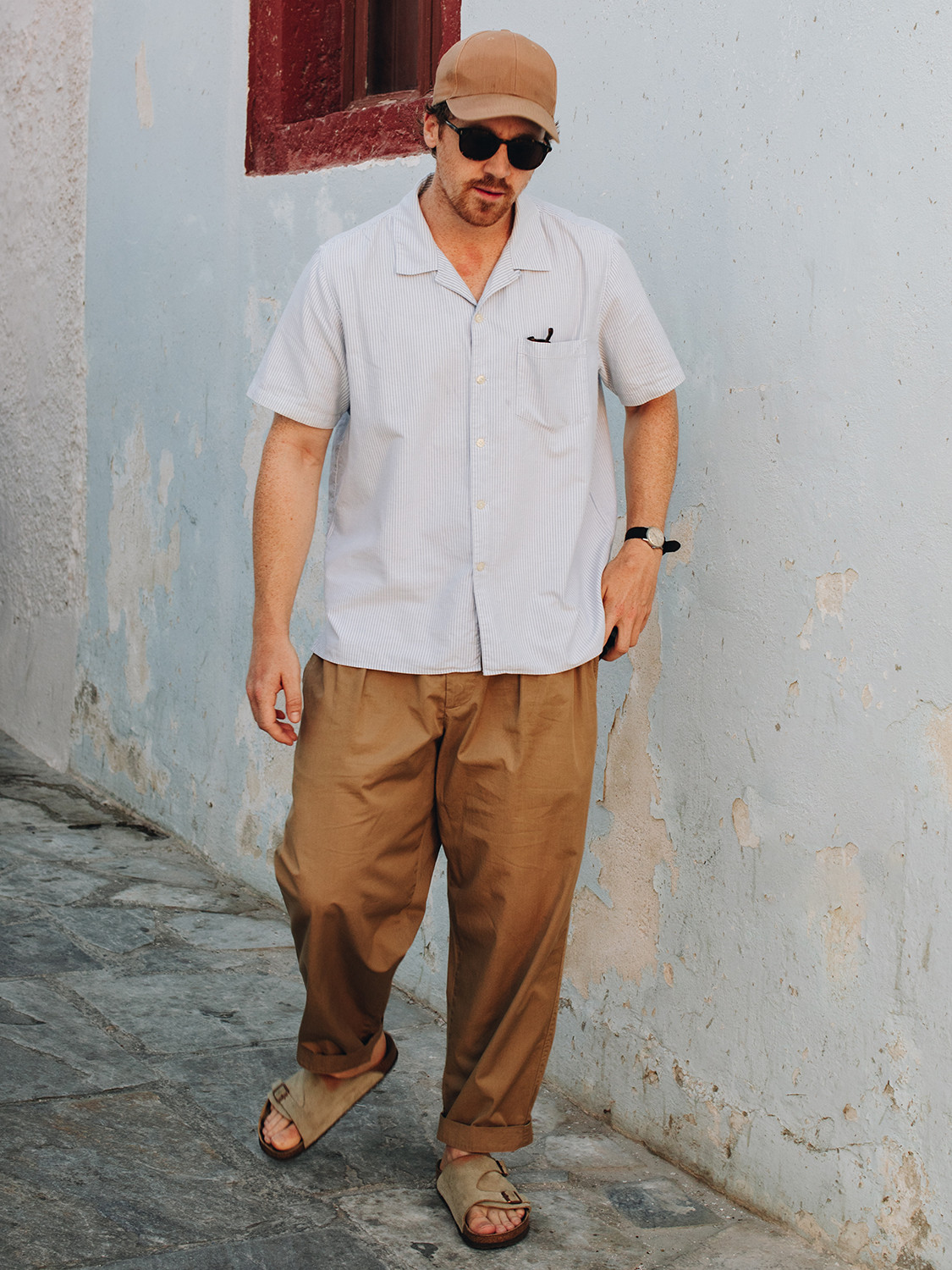 Men's outfit idea for 2021 with blue short-sleeved plain shirt, neutral chinos, black thick framed sunglasses, neutral baseball / snapback cap. Suitable for summer.