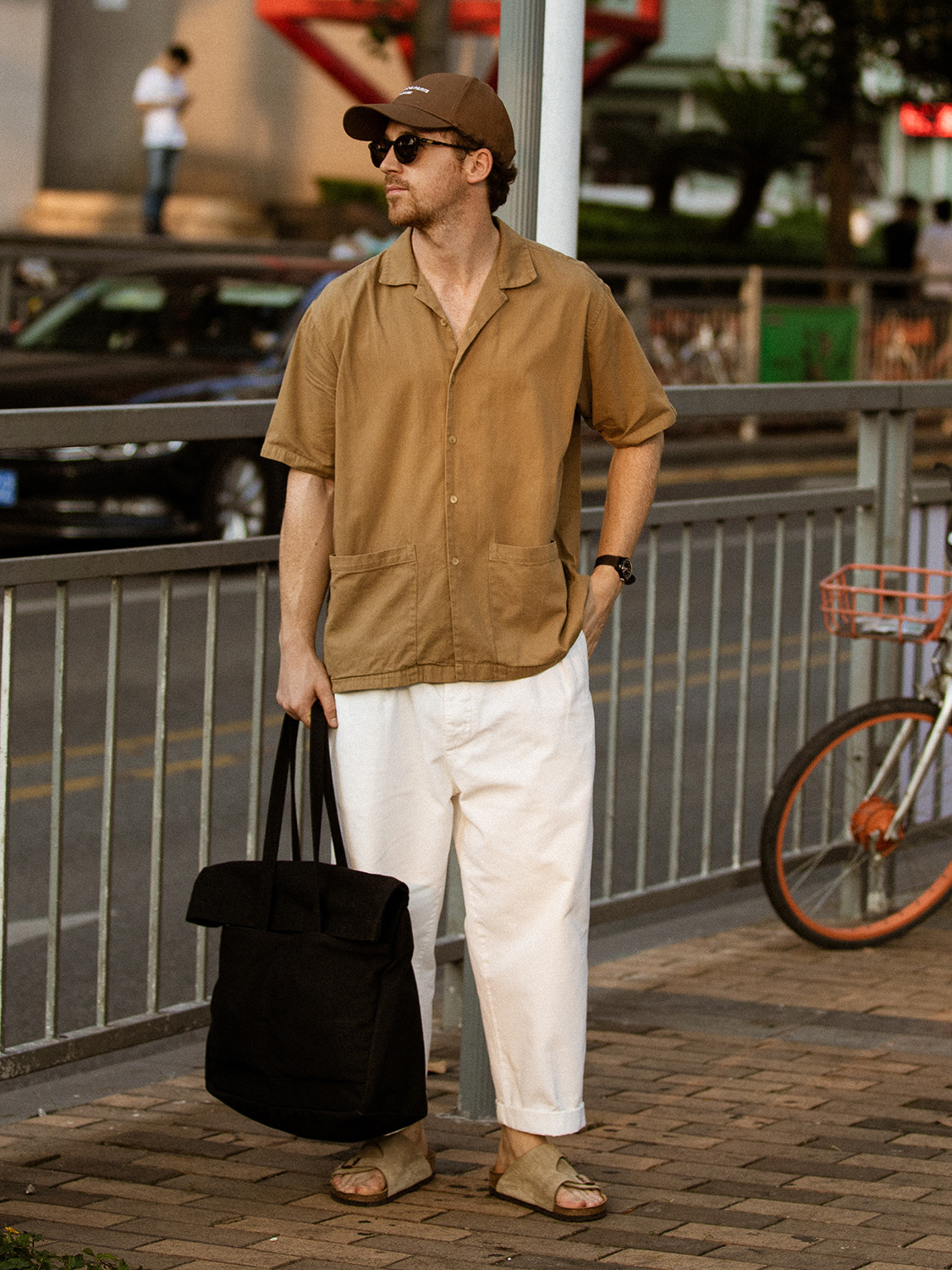 Men's outfit idea for 2021 with neutral short-sleeved plain shirt, white chinos, brown baseball / snapback cap. Suitable for summer.