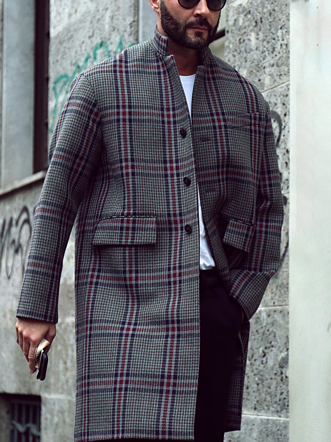 Men's outfit idea for 2021 with grey single-breasted overcoat, white long-sleeved t-shirt, black chinos, black sunglasses, black trainers. Suitable for autumn and winter.