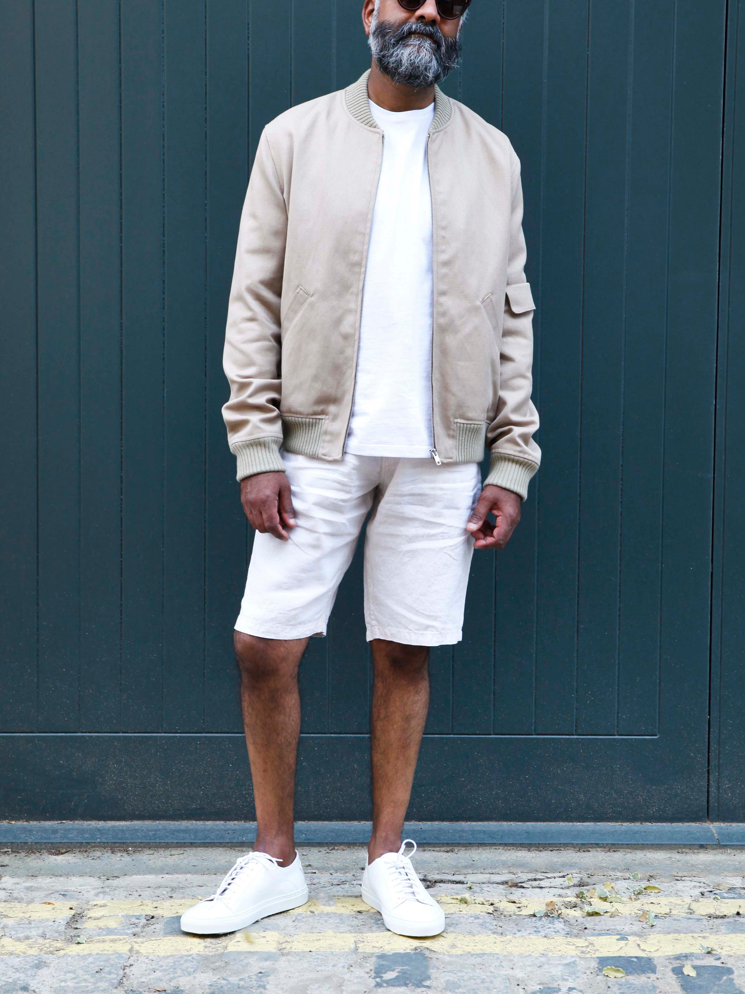 Men's outfit idea for 2021 with bomber jacket, white crew neck t-shirt, stone shorts, white trainers. Suitable for summer.