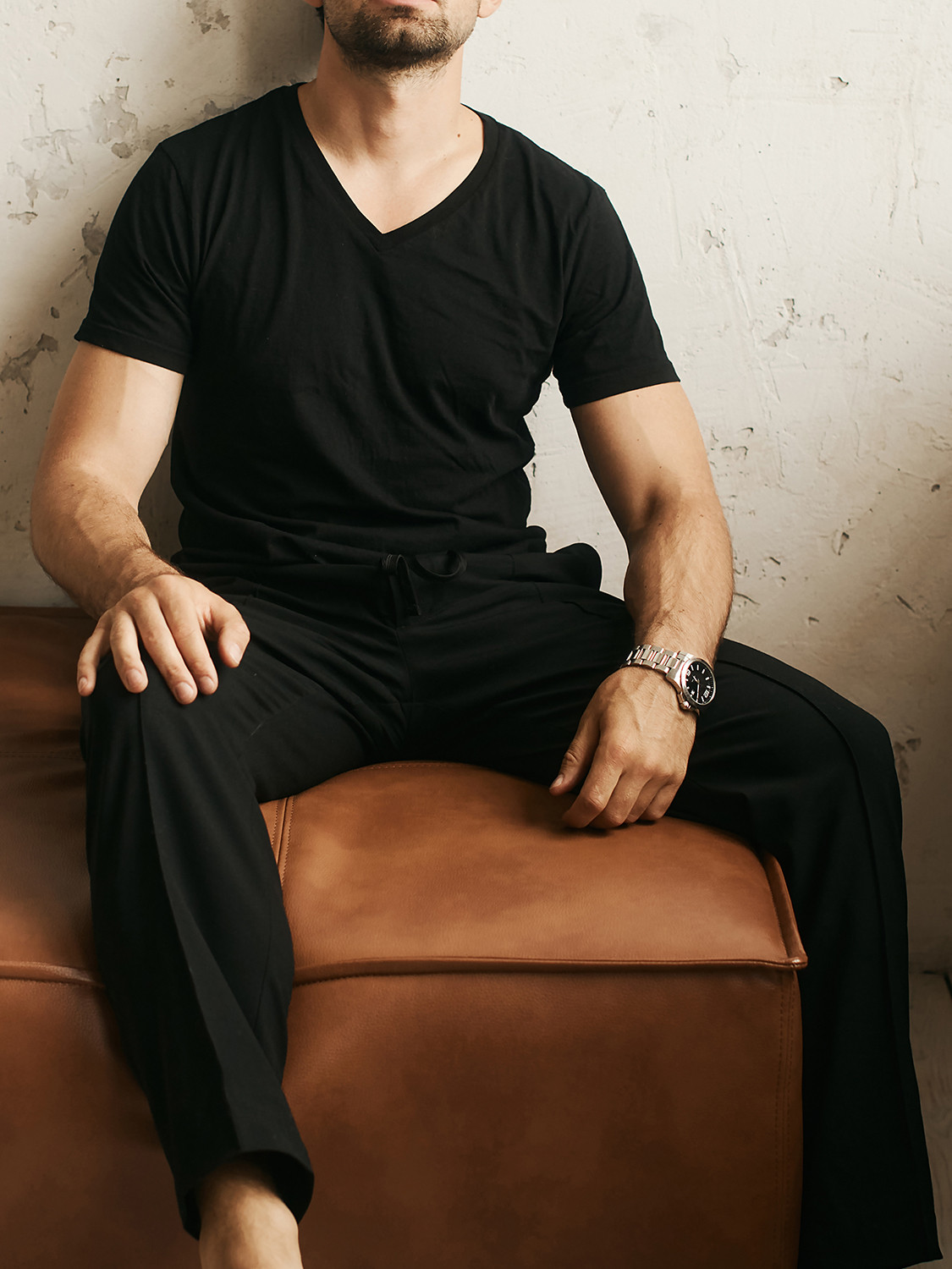 Men's outfit idea for 2021 with black plain v-neck t-shirt, black chinos, metallic chain-link watch, black sandals. Suitable for spring and summer.