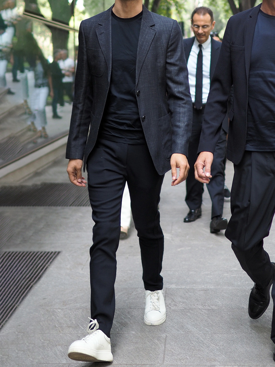 Men's outfit idea for 2021 with navy textured blazer, navy crew neck t-shirt, navy formal trousers, white trainers. Suitable for spring, summer and autumn.
