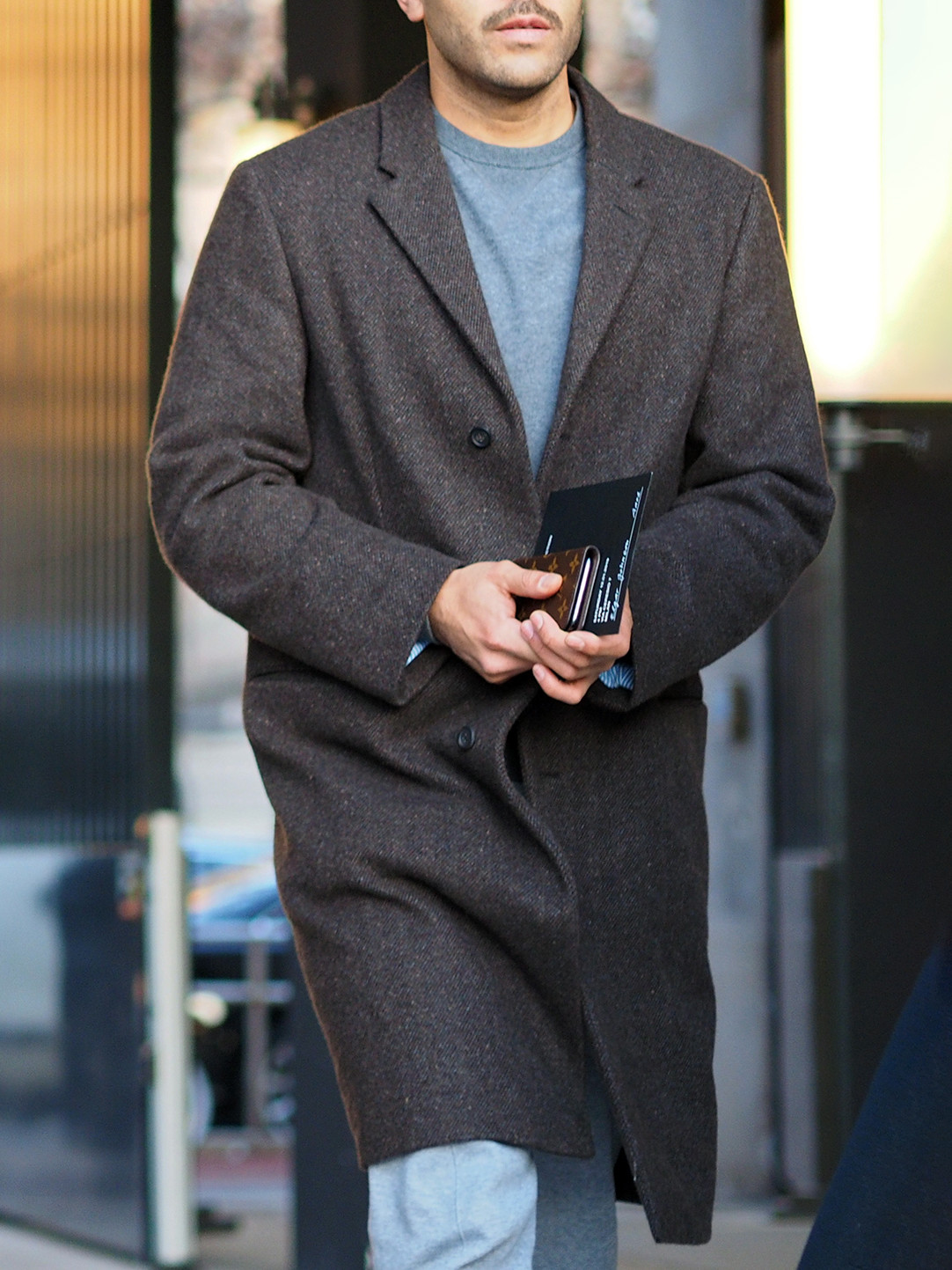 Men's outfit idea for 2021 with grey single-breasted overcoat, blue plain crew neck knitted sweater, light blue jeans, neutral chelsea boots. Suitable for fall and winter.