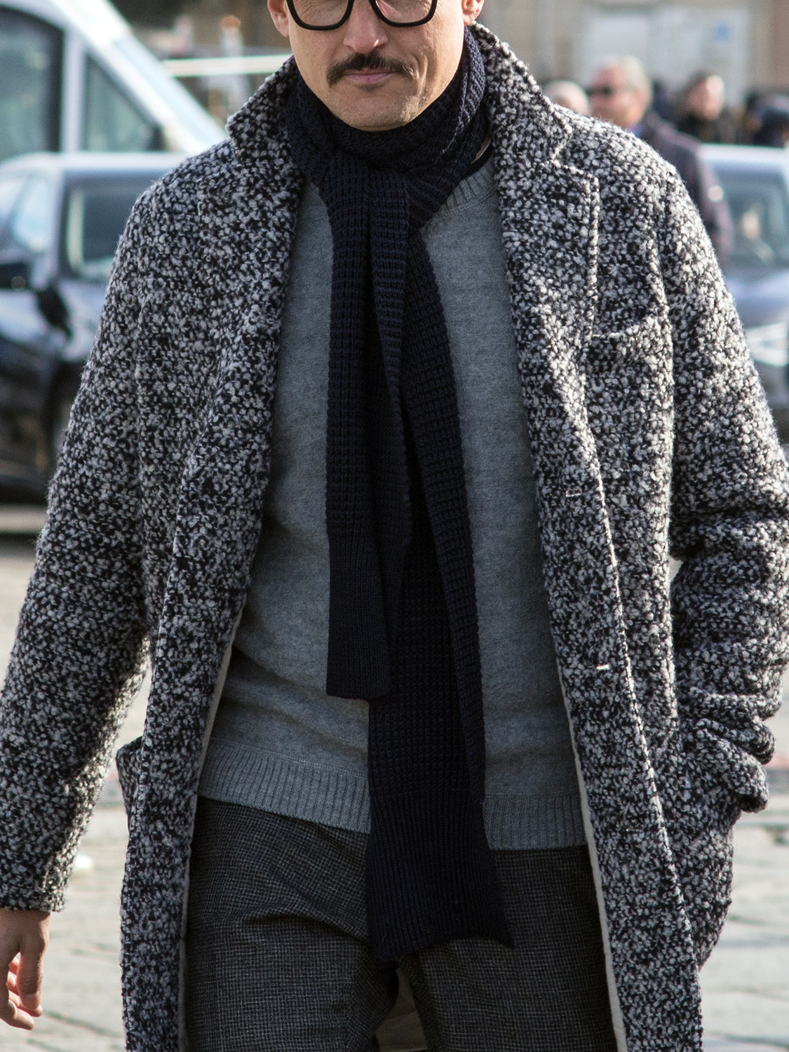 Men's outfit idea for 2021 with grey plain crew neck knitted jumper, grey patterned formal trousers, navy plain knitted scarf, black monk-strap shoes. Suitable for autumn and winter.