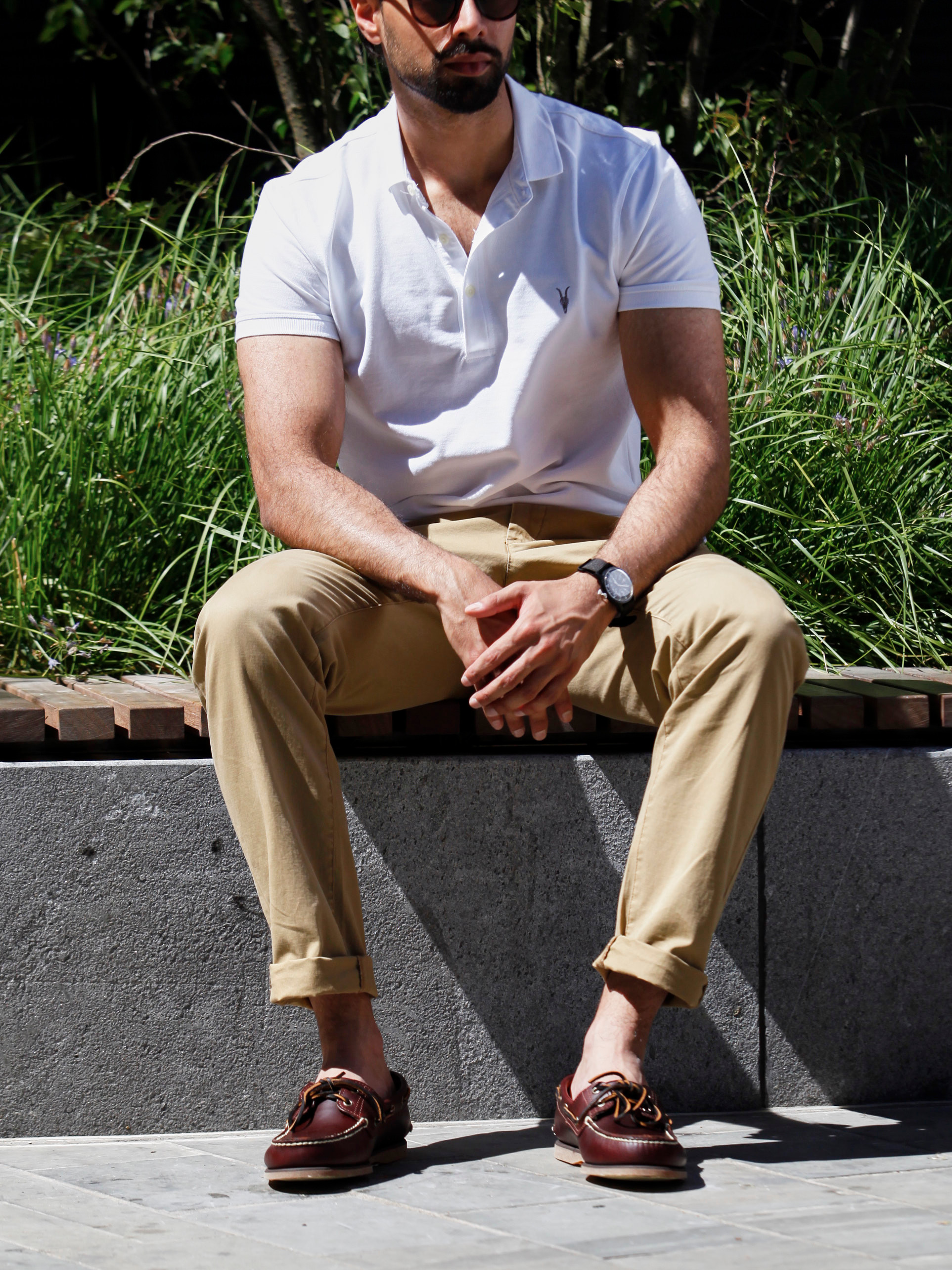 Men's outfit idea for 2021 with white polo, stone chinos, brown boat shoes. Suitable for spring and summer.