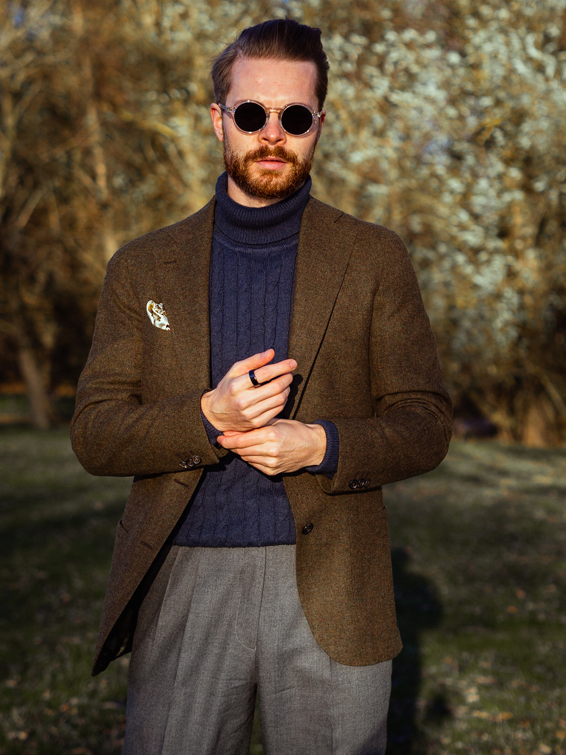 Men's outfit idea for 2021 with brown blazer, navy heavyweight rollneck sweater, grey plain dress pants, black monk-strap shoes. Suitable for fall and winter.