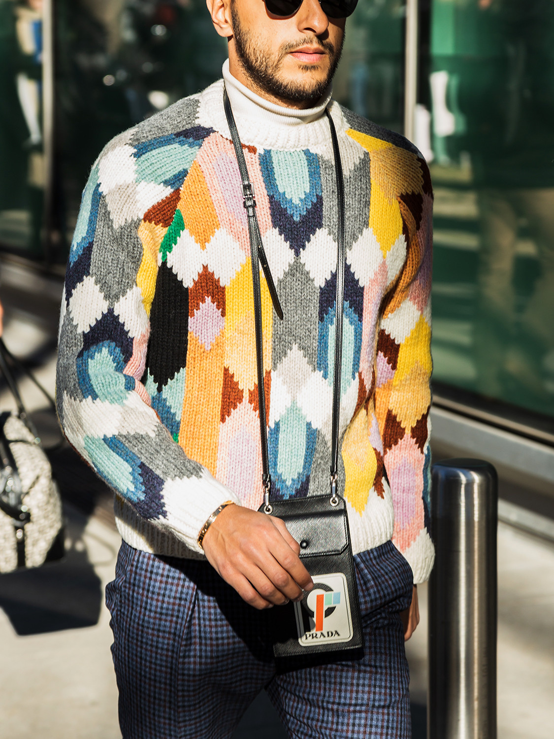 Men's outfit idea for 2021 with multicoloured patterned jumper, navy patterned formal trousers, white trainers. Suitable for spring, autumn and winter.