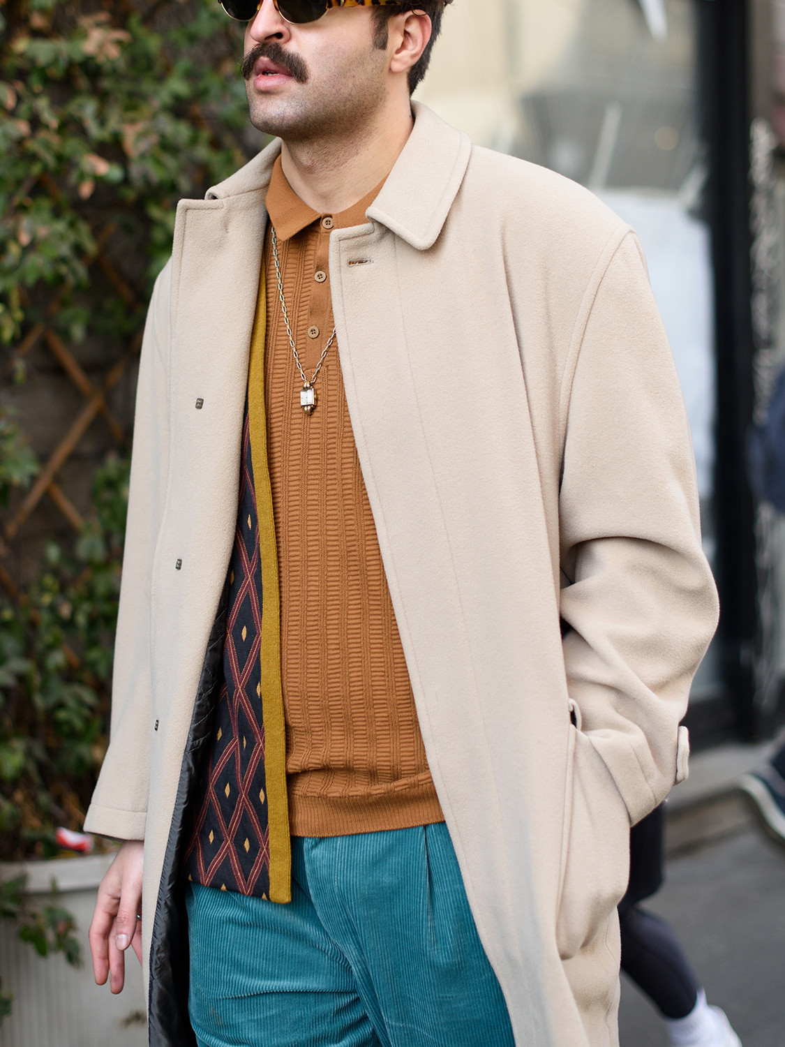 Men's outfit idea for 2021 with camel coat, brown long-sleeved polo, blue chinos, tortoiseshell sunglasses, oxford / derby shoes. Suitable for autumn and winter.