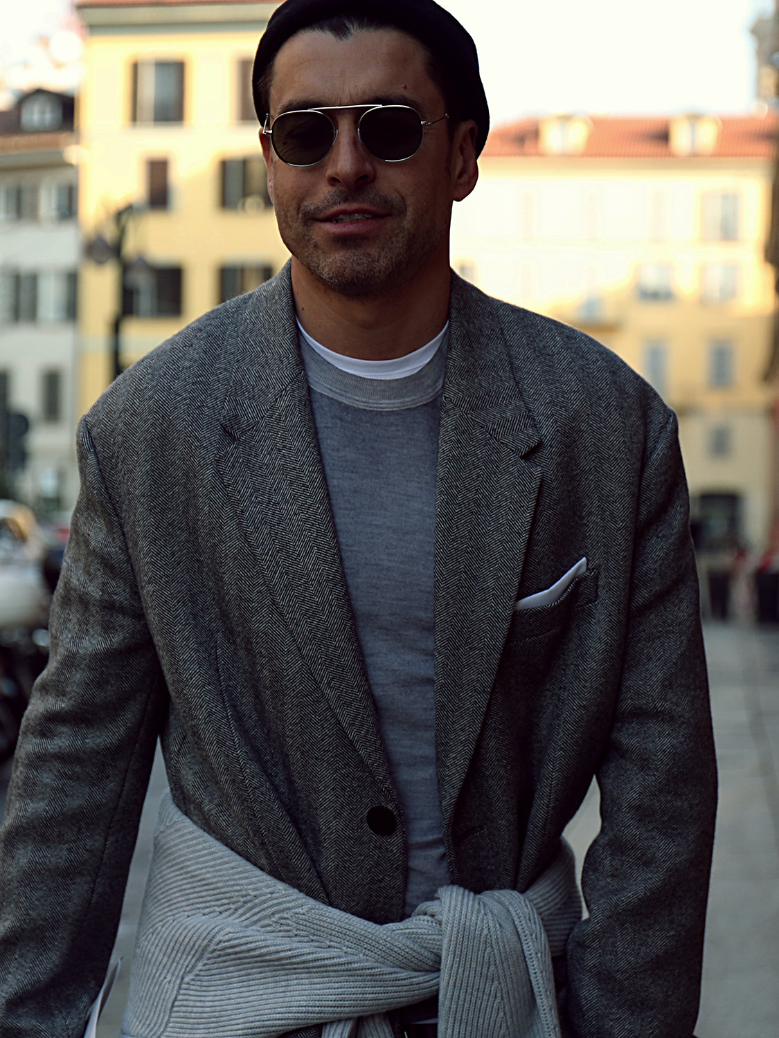 Men's outfit idea for 2021 with grey textured blazer, grey crew neck knitted jumper, white crew neck t-shirt, dark blue jeans, black loafers. Suitable for spring, autumn and winter.