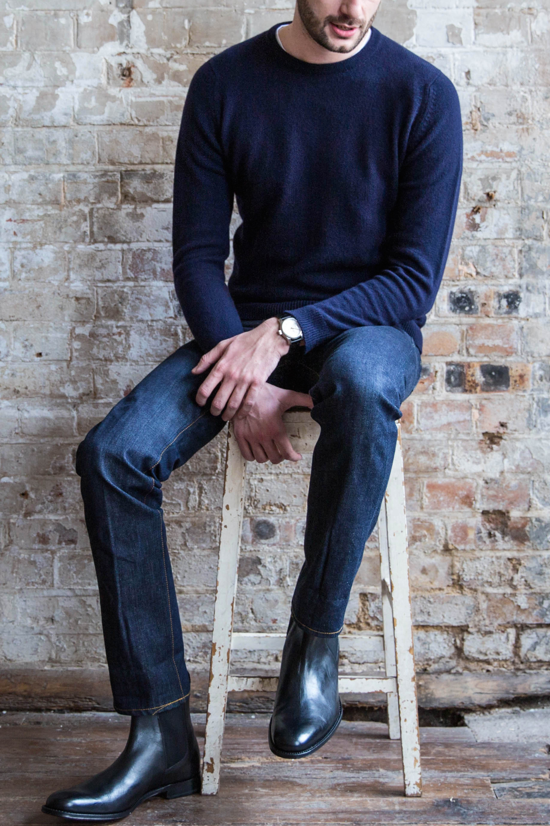 Men's outfit idea for 2021 with navy crew neck knitted sweater, dark blue jeans, leather strap watch, black chelsea boots. Suitable for spring, fall and winter.