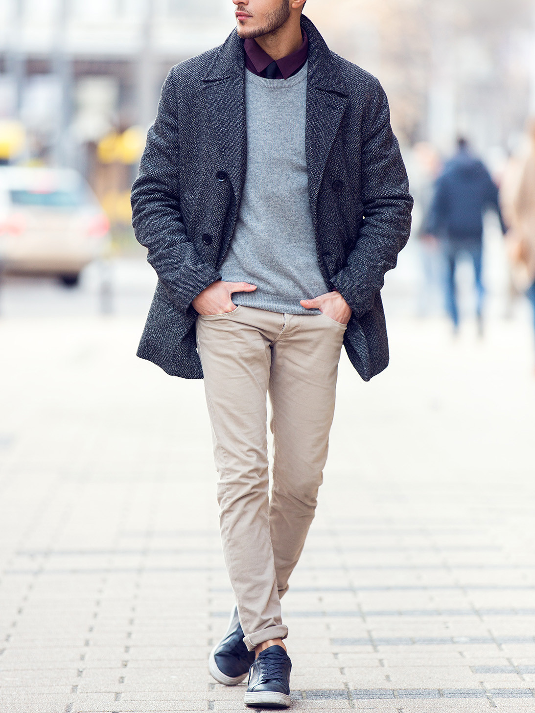 Men's outfit idea for 2021 with navy pea coat, grey plain crew neck knitted jumper, navy plain casual shirt, stone chinos, navy everyday trainers. Suitable for autumn and winter.