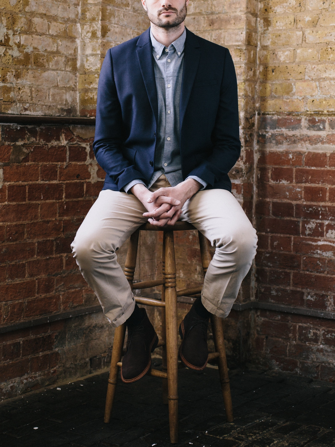 Men's outfit idea for 2021 with navy blazer, blue casual shirt, stone chinos, brown desert boots. Suitable for spring and fall.