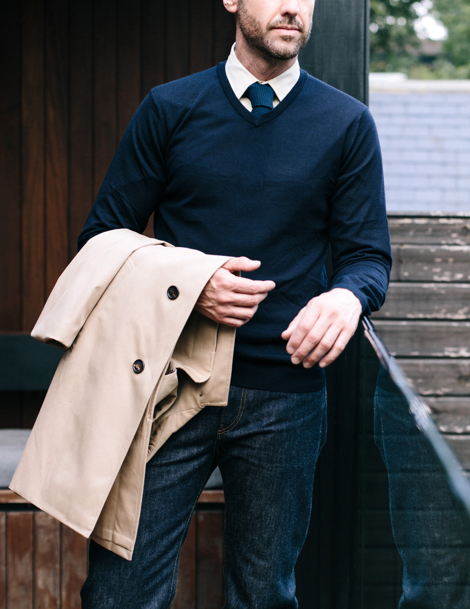 Men's outfit idea for 2021 with stone trench coat, navy v-neck sweater, white dress shirt, dark blue jeans. Suitable for spring, fall and winter.
