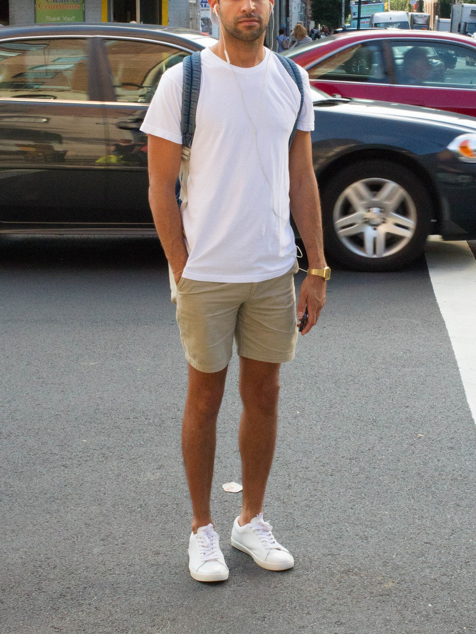 Men's outfit idea for 2021 with white crew neck t-shirt, stone shorts, black sunglasses, white trainers. Suitable for summer.