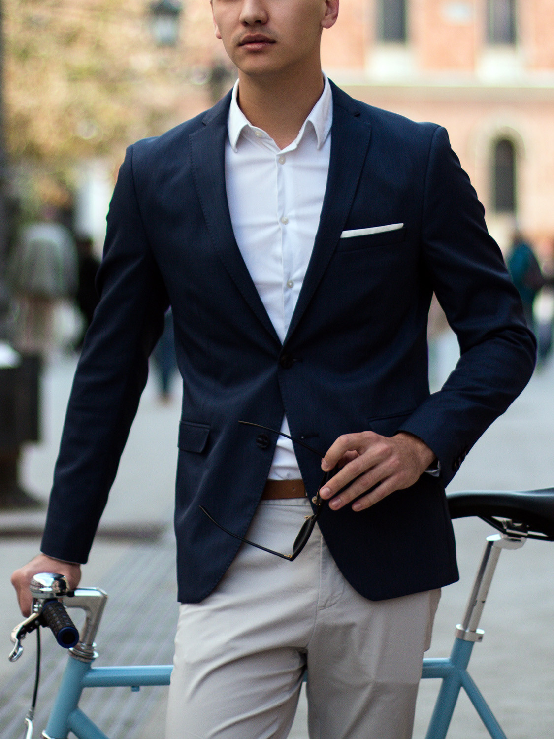 Men's outfit idea for 2021 with navy plain blazer, white plain casual shirt, neutral chinos, brown casual belt, brown brogues. Suitable for spring and autumn.