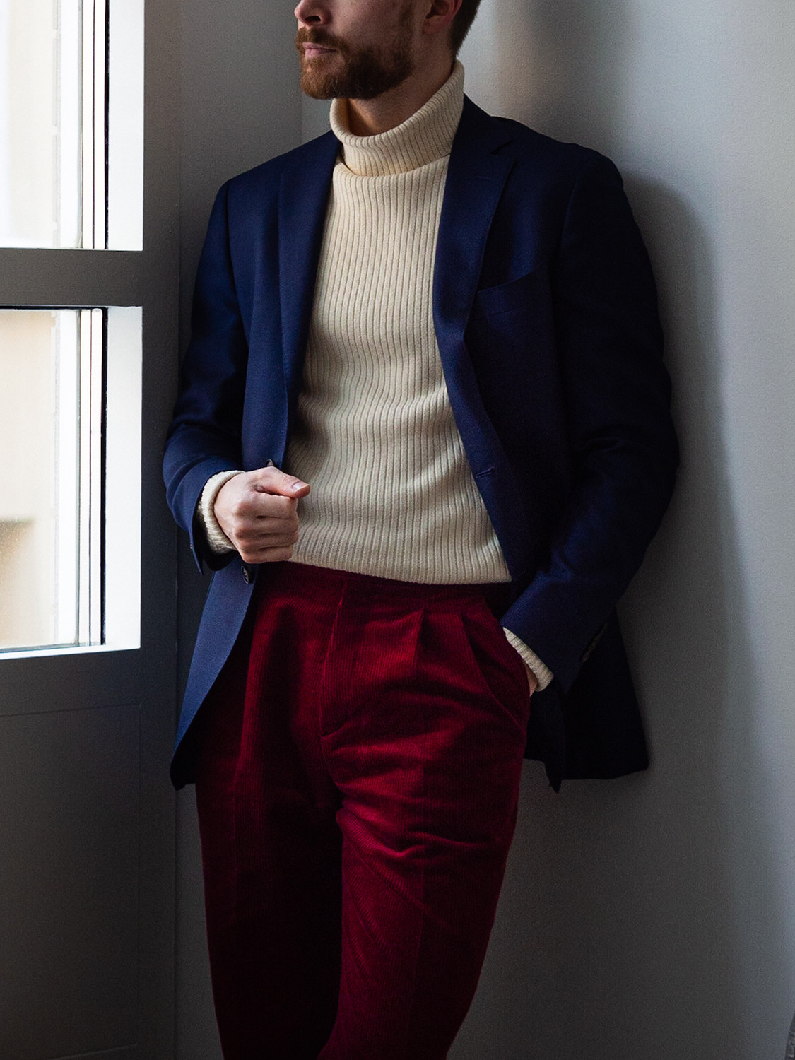 Men's outfit idea for 2021 with navy plain blazer, heavyweight rollneck jumper, red plain formal trousers, brown brogues. Suitable for autumn and winter.