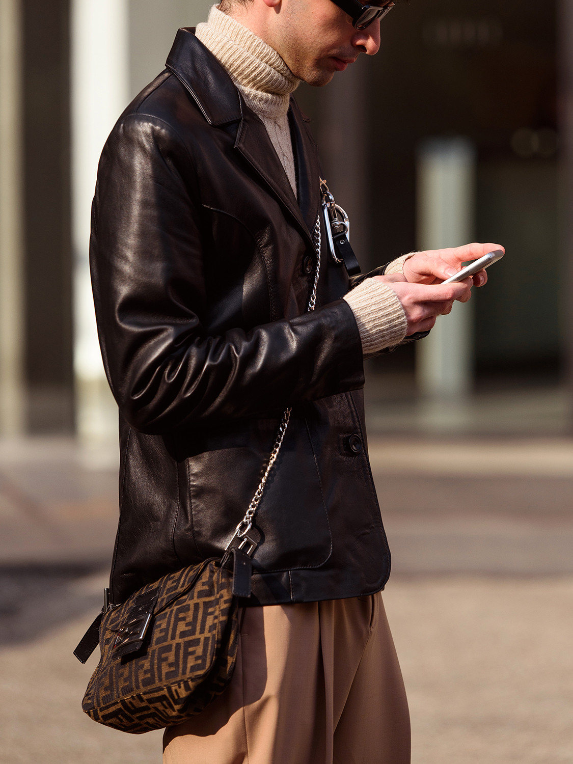 Men's outfit idea for 2021 with brown leather jacket, neutral lightweight rollneck jumper, neutral chinos, black sunglasses, converse. Suitable for autumn and winter.