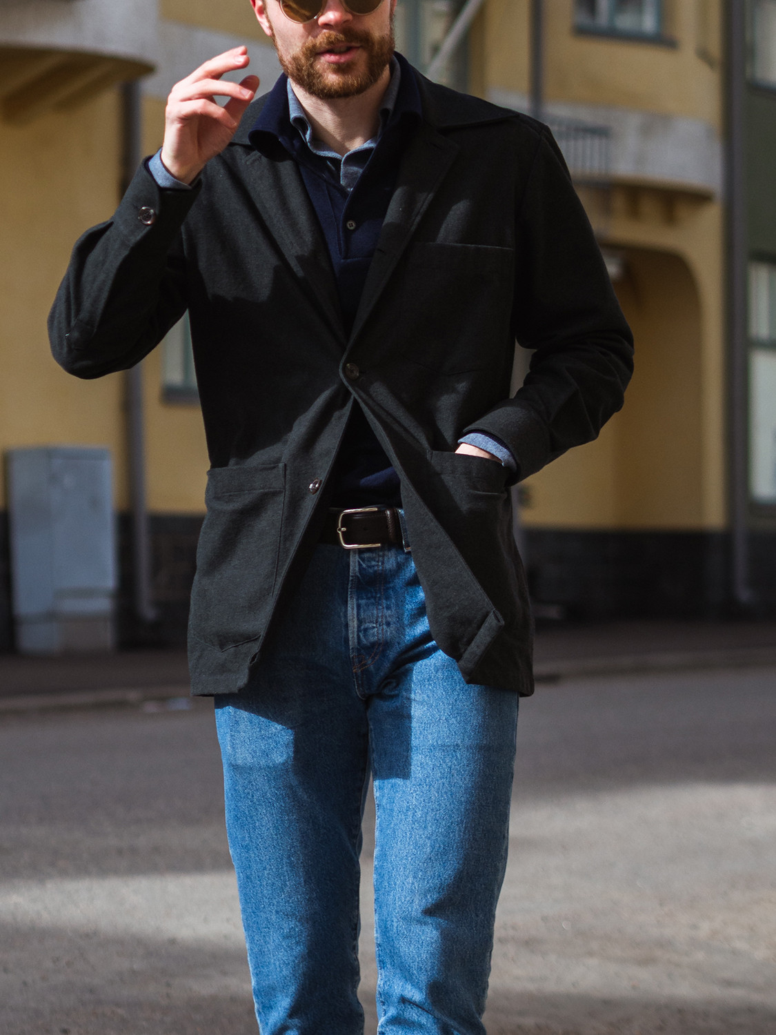 Men's outfit idea for 2021 with black unstructured blazer, mid blue jeans, black sunglasses, lace-up leather boots. Suitable for spring and autumn.