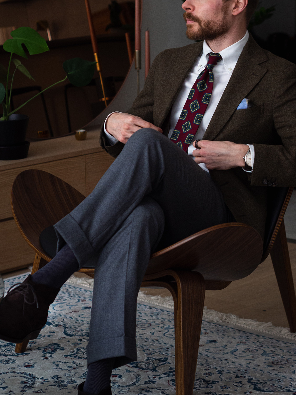 Men's outfit idea for 2021 with brown blazer, white plain casual shirt, grey plain formal trousers, red patterned tie, black desert boots. Suitable for autumn and winter.