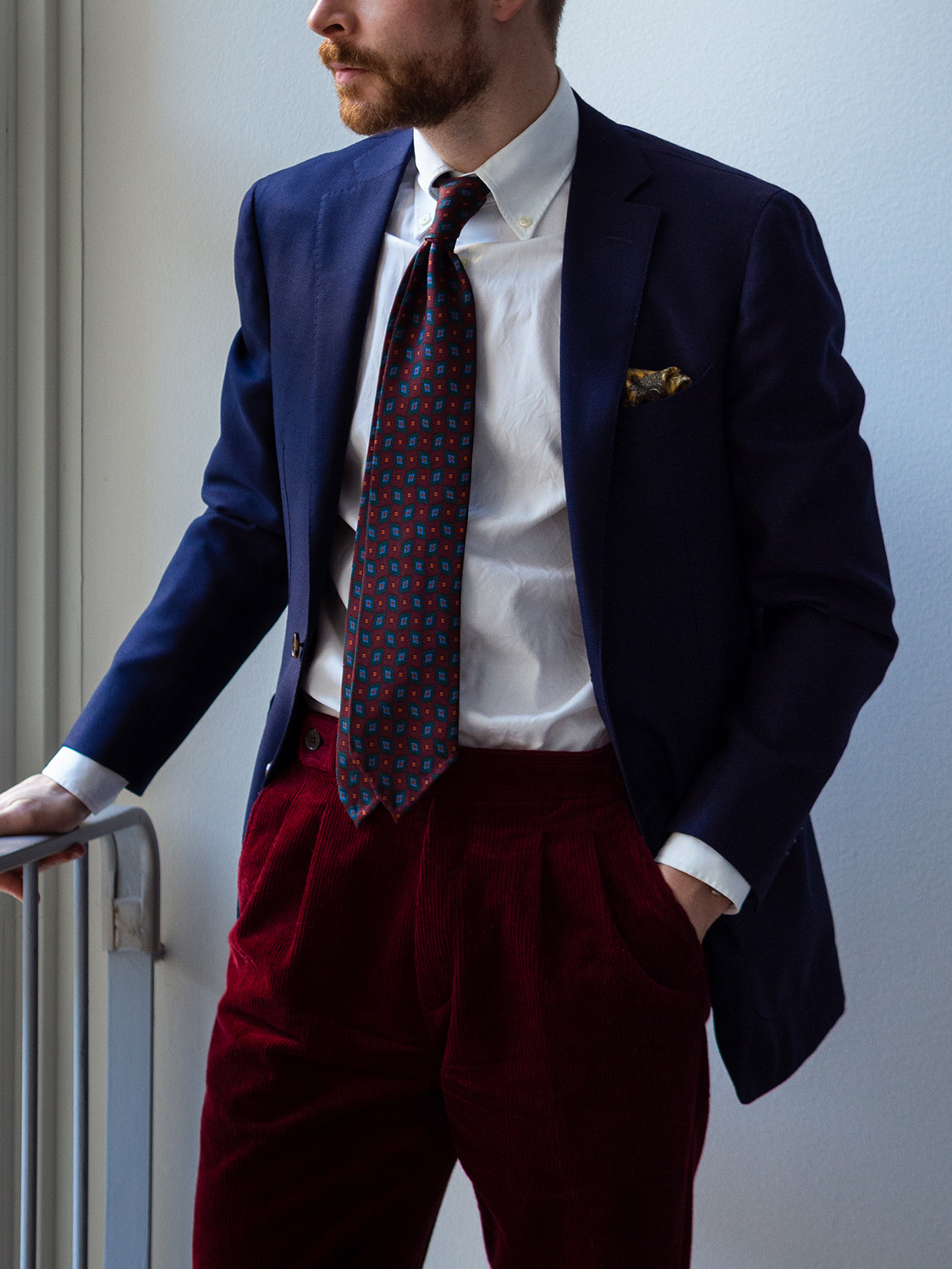 Men's outfit idea for 2021 with blue plain blazer, white plain casual shirt, red chinos, red patterned tie, oxford / derby shoes. Suitable for spring, summer and autumn.