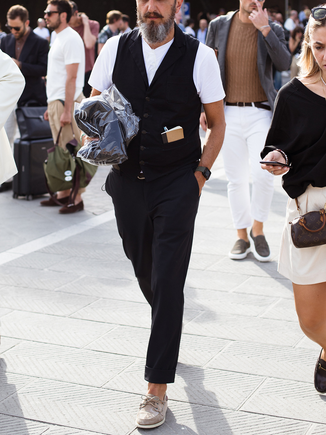 Men's outfit idea for 2021 with black waistcoat, white crew neck t-shirt, black plain formal trousers, grey boat shoes. Suitable for spring and summer.