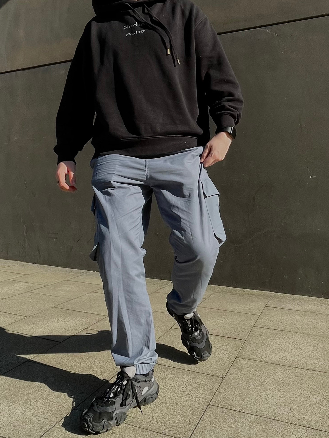 Men's outfit idea for 2021 with black logo / printed hoodie, grey cargo pants, black sneakers. Suitable for spring and fall.