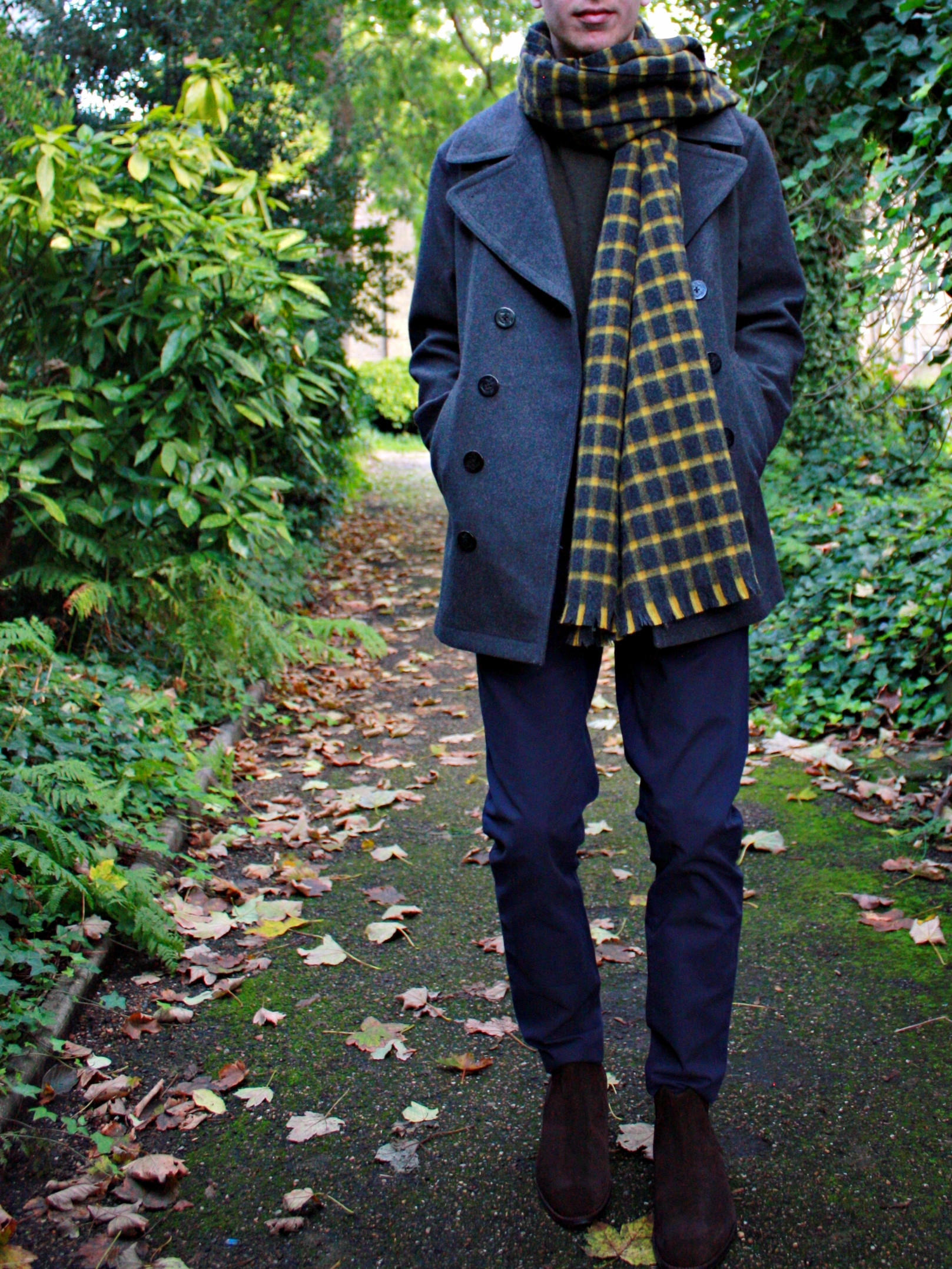 Men's outfit idea for 2021 with navy pea coat, bold coloured crew neck jumper, navy chinos, patterned knitted scarf, brown chelsea boots. Suitable for autumn and winter.