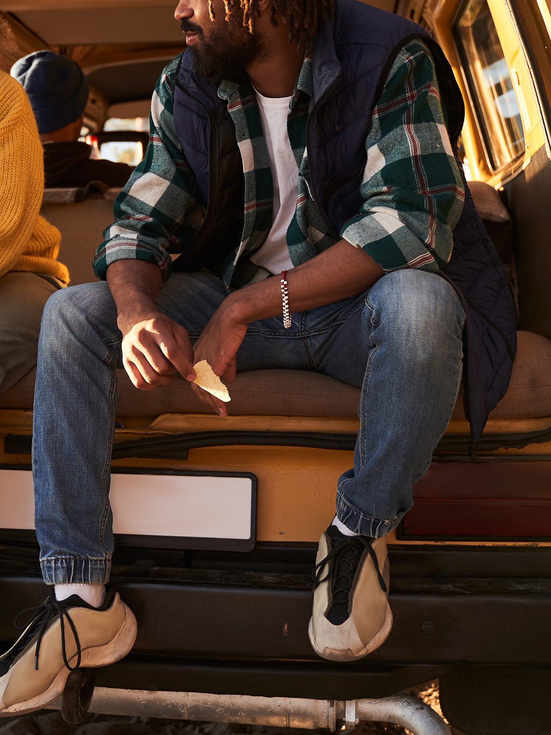 Men's outfit idea for 2021 with navy vest, green plaid shirt, white crew neck t-shirt, mid blue jeans. Suitable for spring and fall.