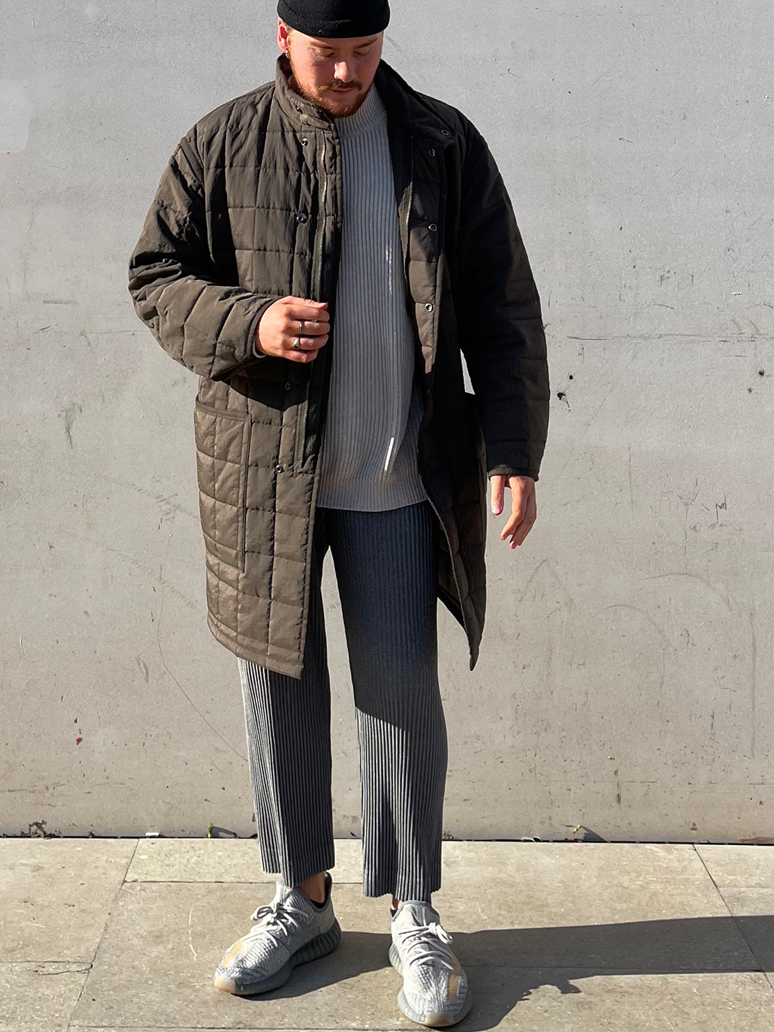 Men's outfit idea for 2021 with green down coat, grey plain crew neck knitted sweater, grey sweatpants, grey sneakers. Suitable for fall and winter.