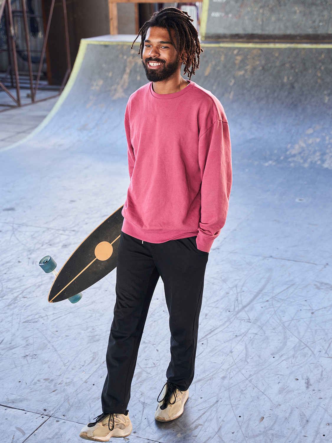 Men's outfit idea for 2021 with pink plain sweatshirt, black trackpants, neutral sneakers. Suitable for spring, summer and fall.