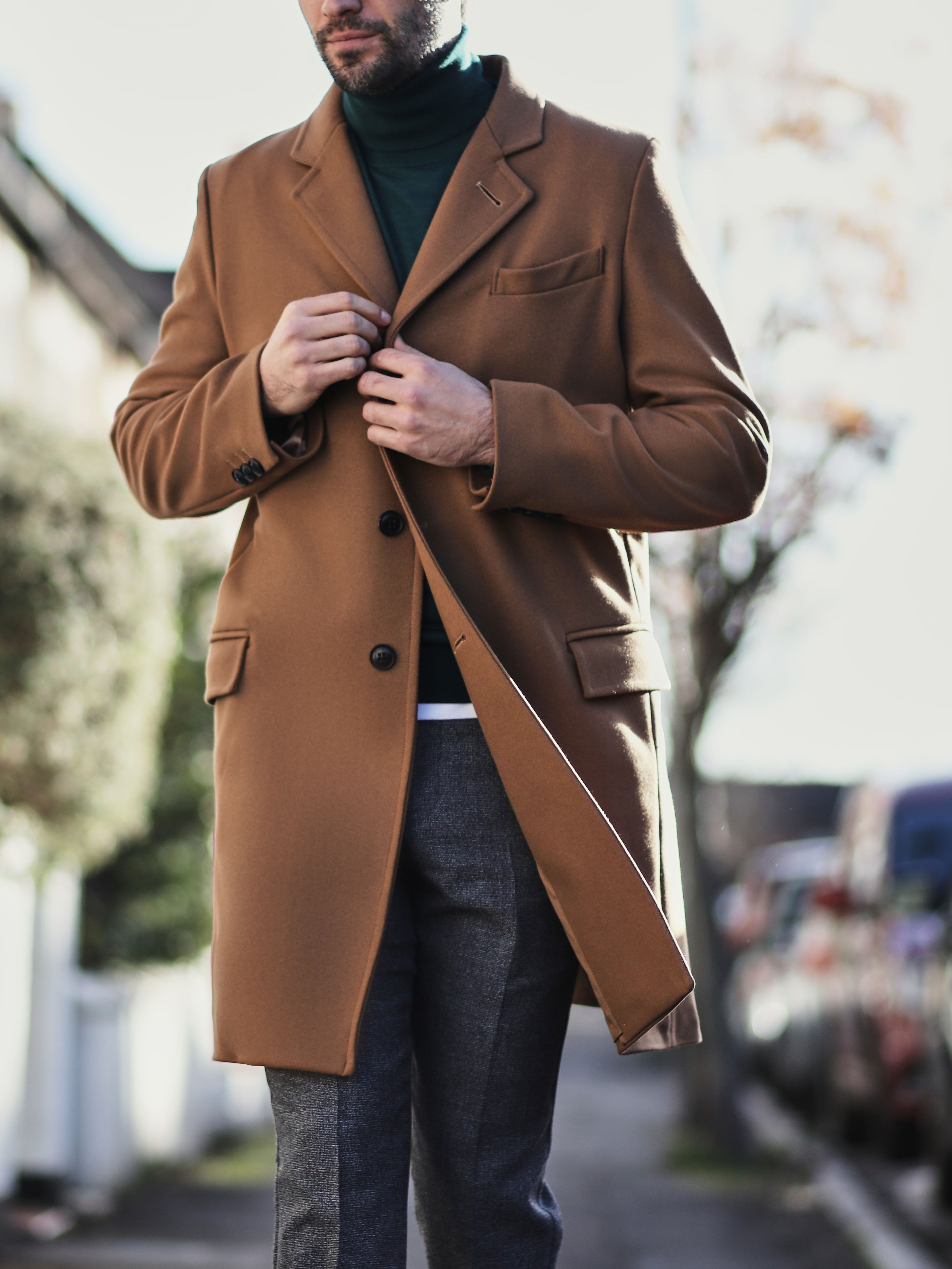 Men's outfit idea for 2021 with camel coat, lightweight rollneck sweater, gray dress pants, brown chelsea boots. Suitable for fall and winter.