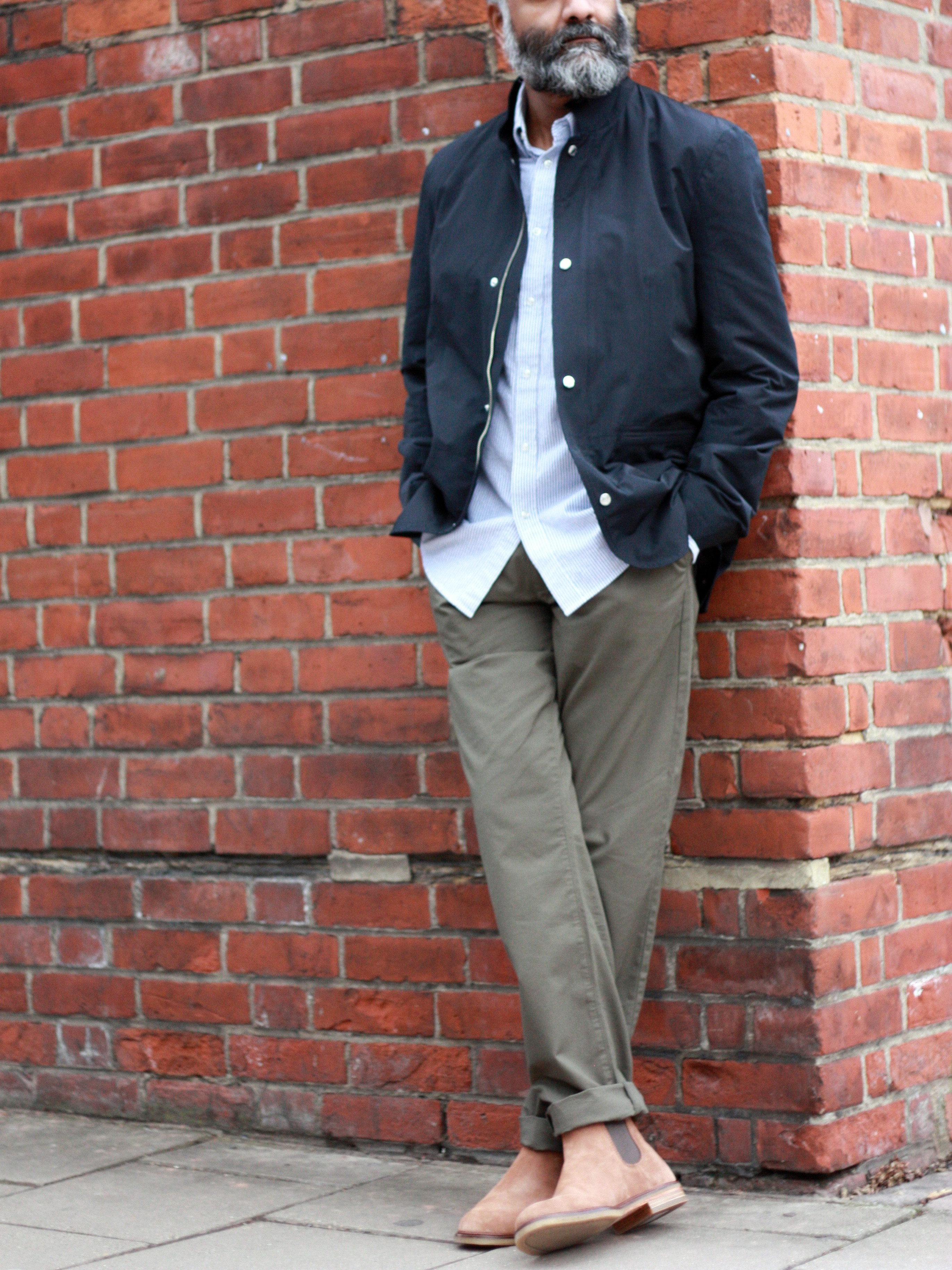 Men's outfit idea for 2021 with utility jacket, striped casual shirt, colored chinos, brown chelsea boots. Suitable for spring, summer and fall.