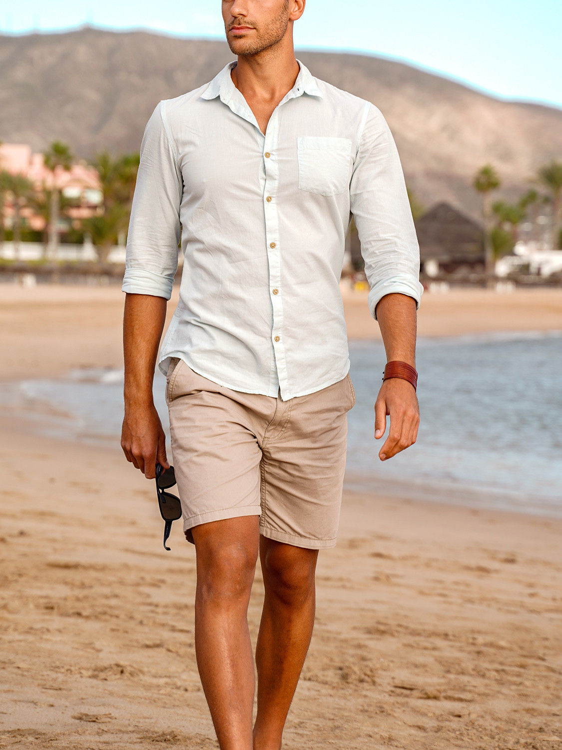 Men's outfit idea for 2021 with blue linen shirt, neutral cotton shorts, brown boat shoes. Suitable for summer.