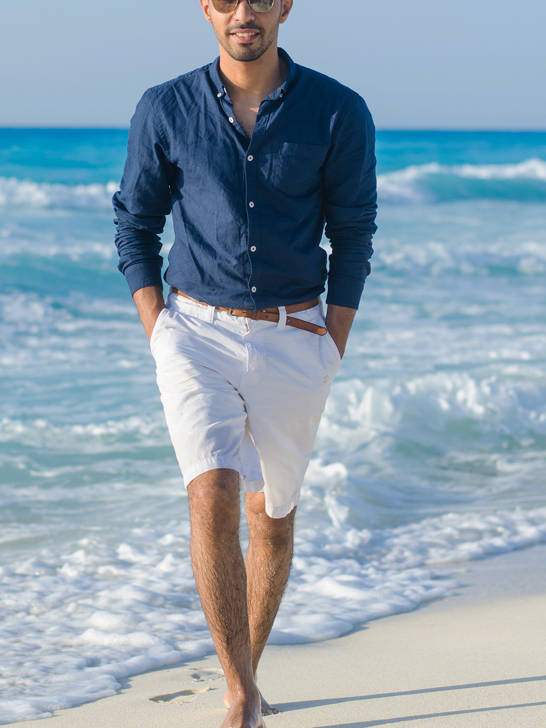 Men's outfit idea for 2021 with blue plain casual shirt, white cotton shorts, brown boat shoes. Suitable for summer.